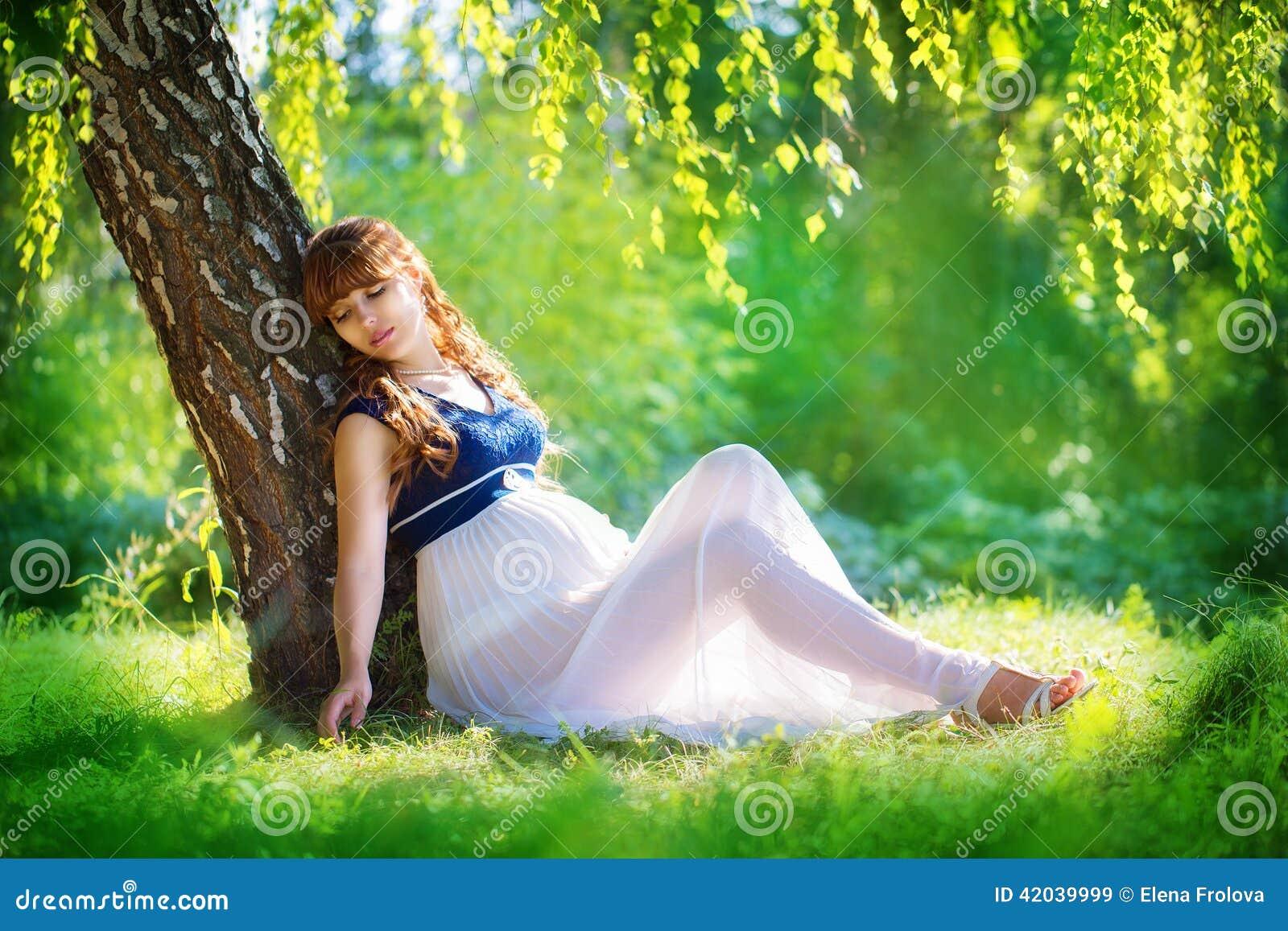 Mulher gravida nova que relaxa no parque fora, pregnanc saudável
