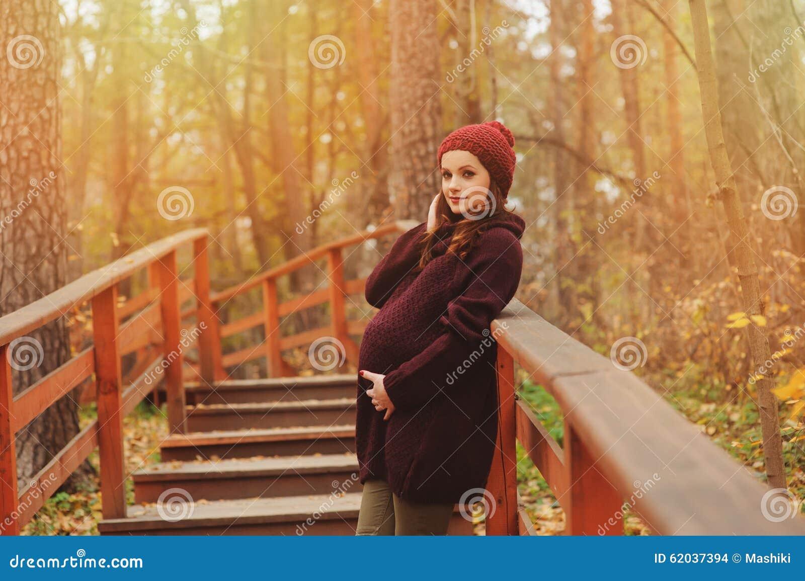 Mulher gravida pensativa no equipamento acolhedor brandamente morno do marsala que anda fora
