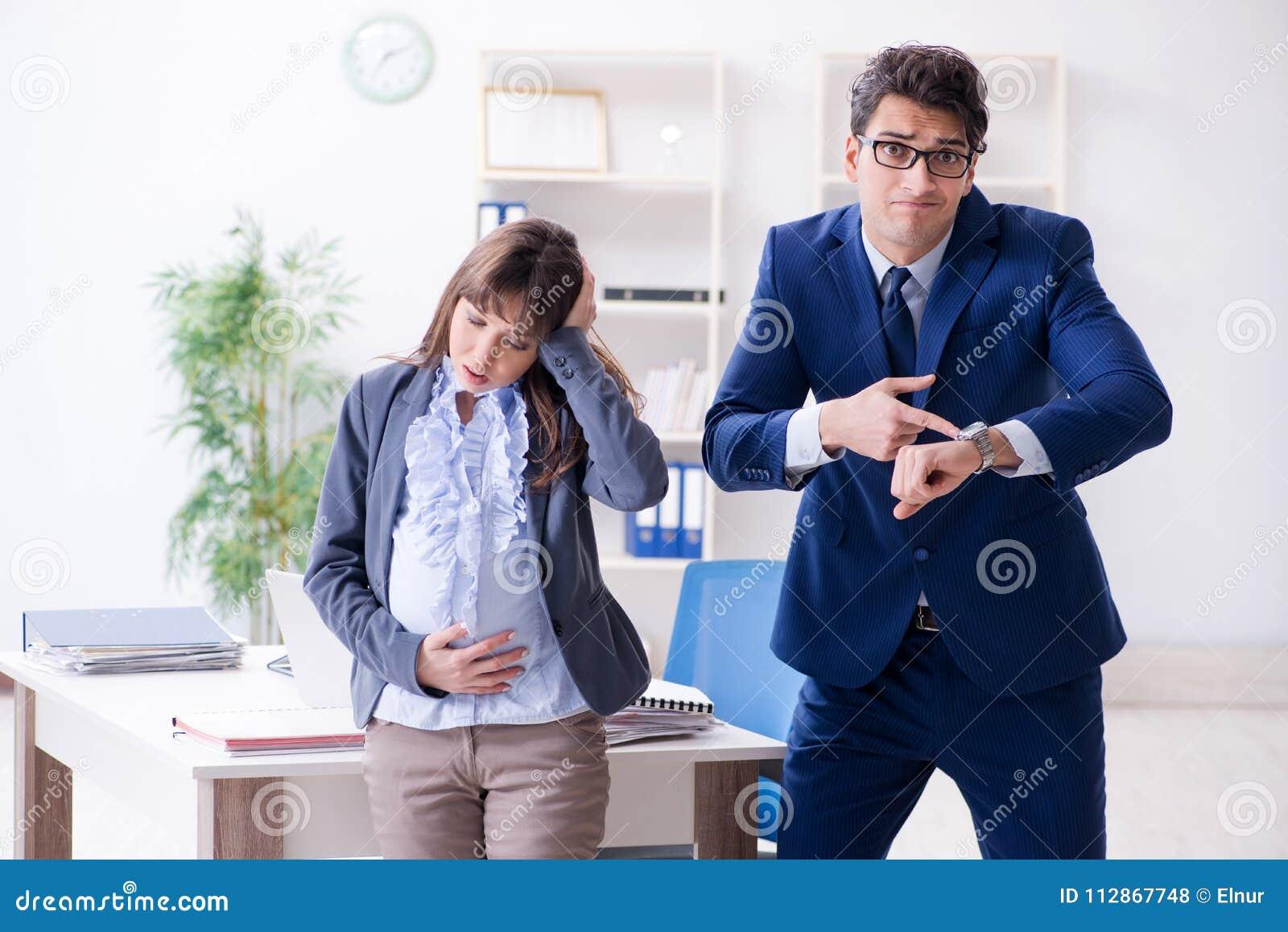 Mulher gravida que esforça-se no escritório e que obtém a colega o