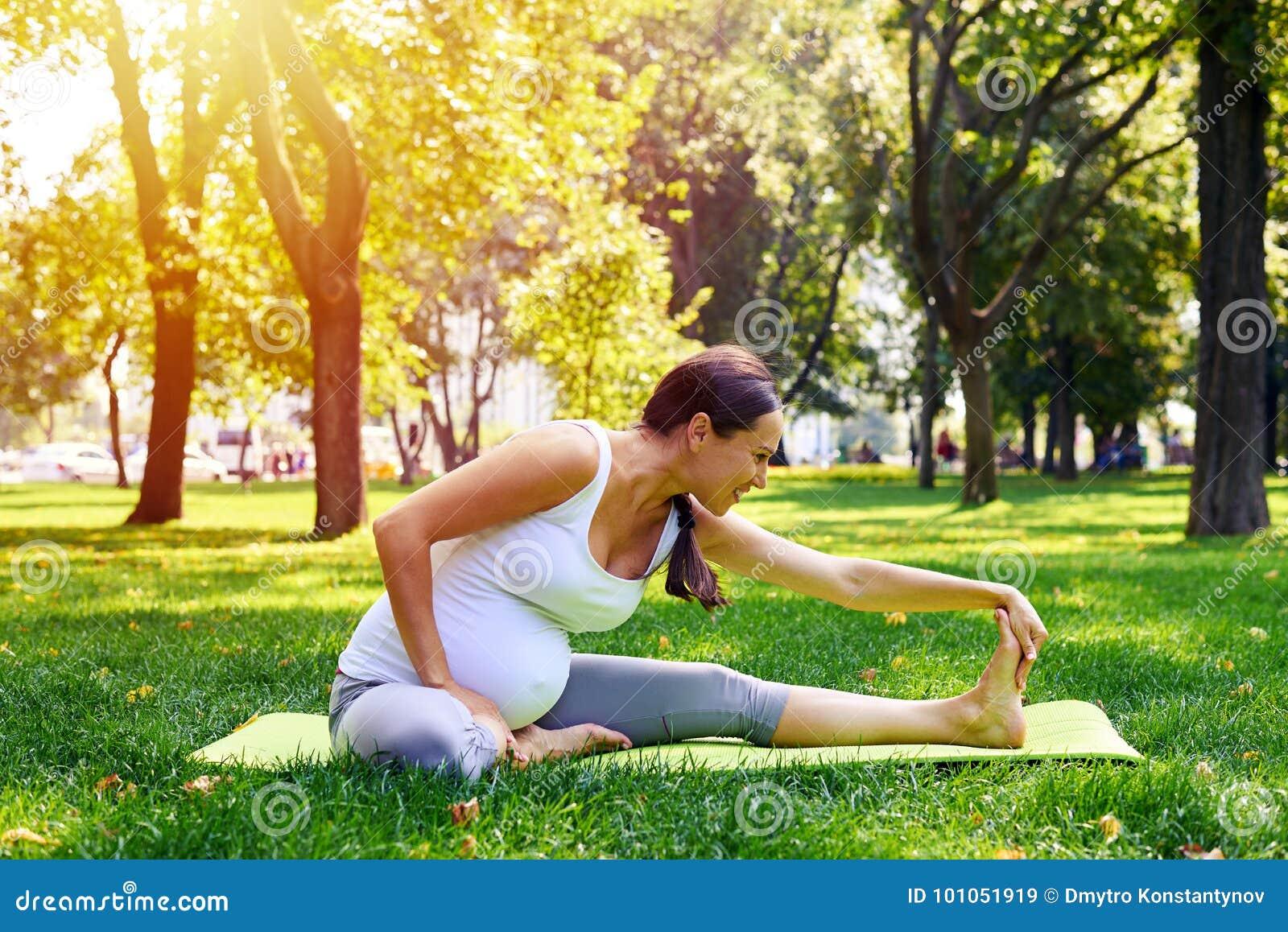 Mulher gravida que faz o exercício de relaxamento da ioga no parque