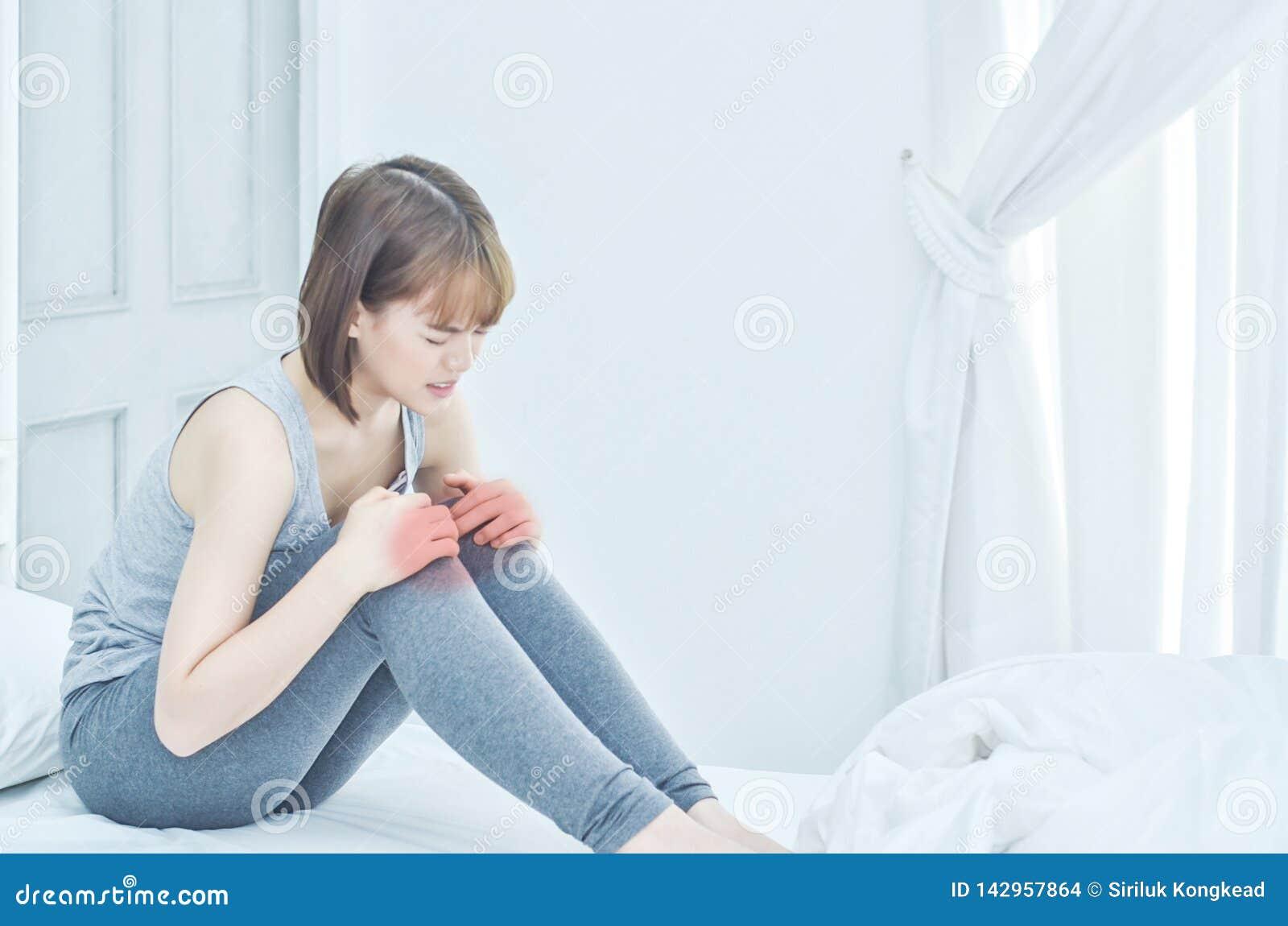 A mulher guardava seu joelho Teve a dor do joelho