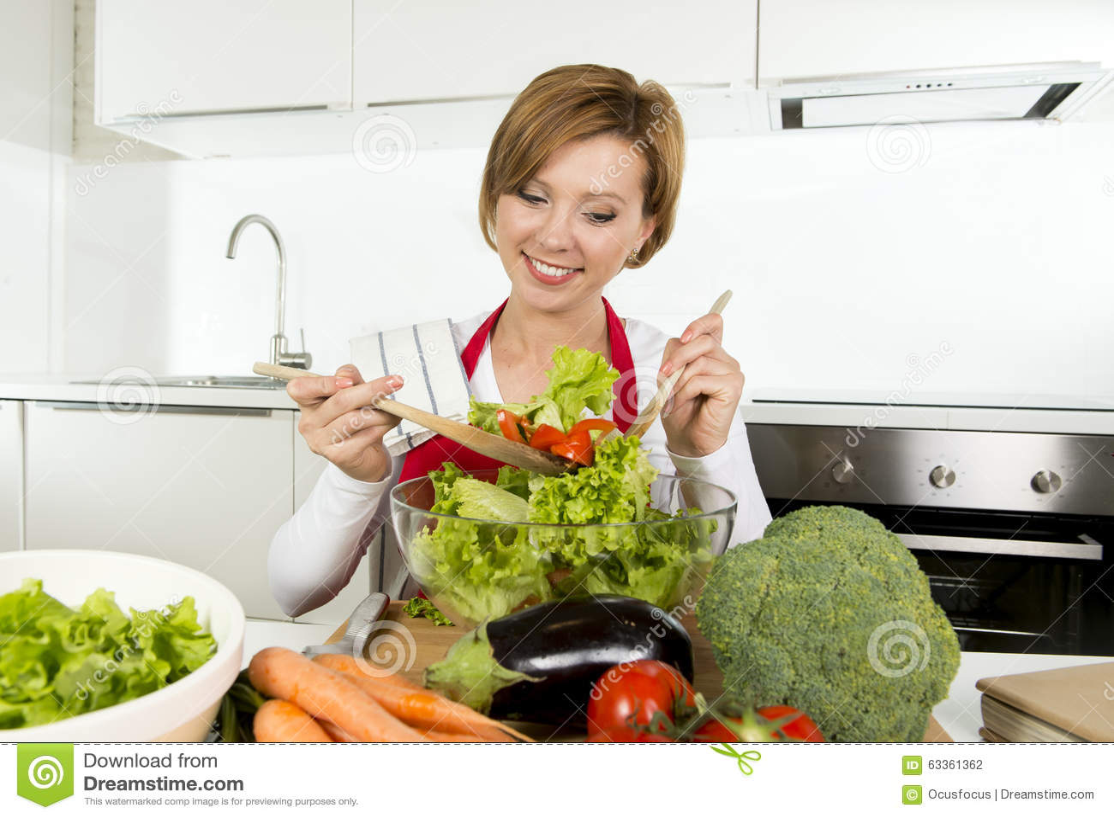 Mulher home bonita nova do cozinheiro na cozinha moderna que prepara o sorriso vegetal da bacia de salada feliz