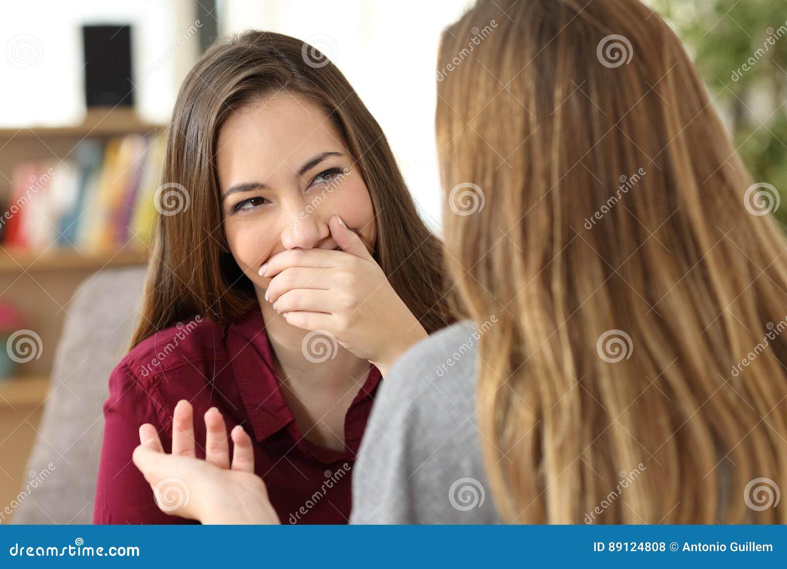 Mulher humilhada que esconde seu sorriso em uma conversação
