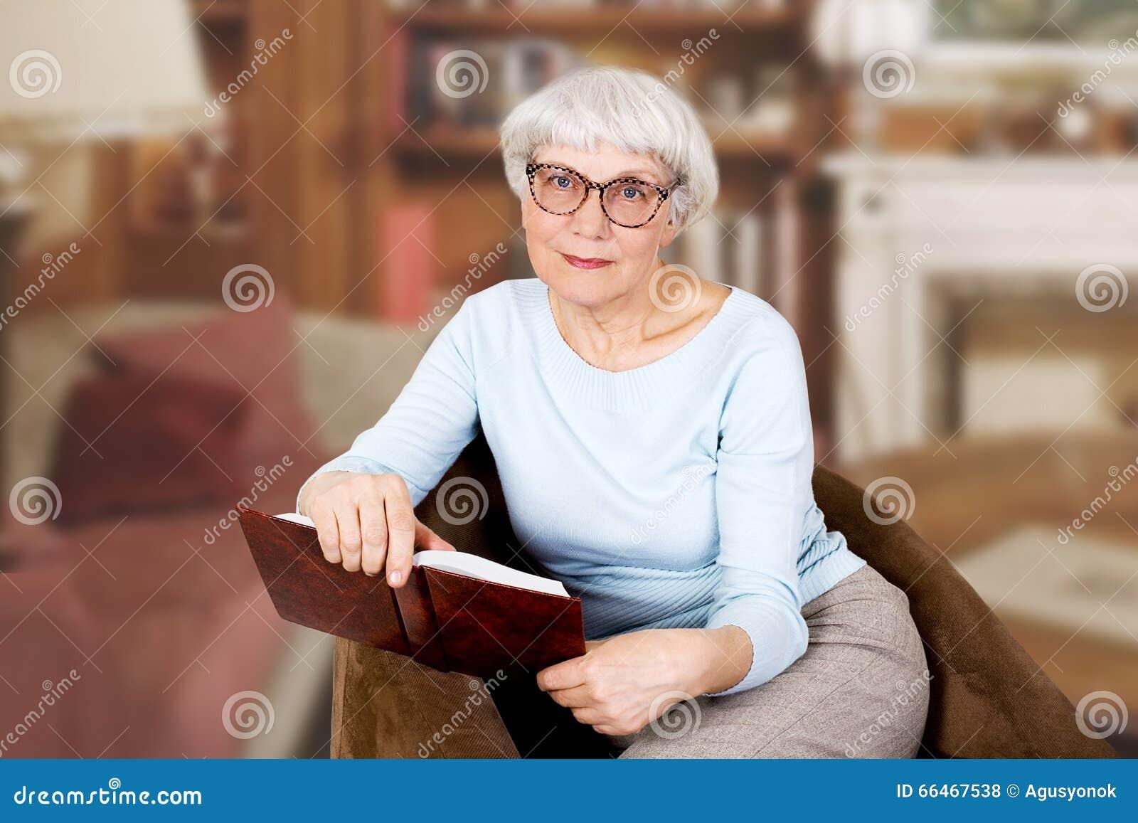 Mulher idosa bonita feliz com o livro e os vidros que sentam-se em uma cadeira matriz avó