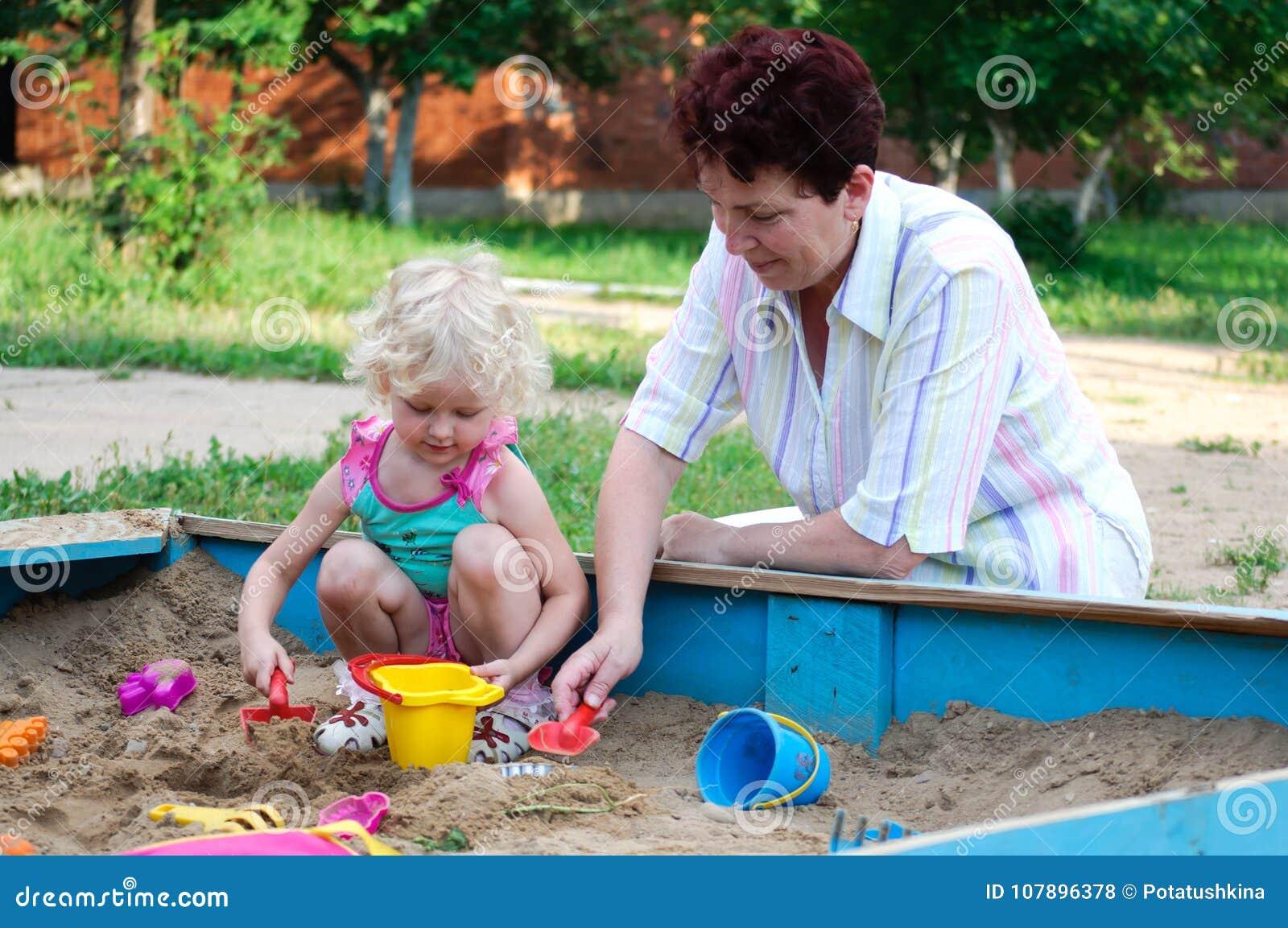 Mulher idosa com jogo devochkaoy no sandpit
