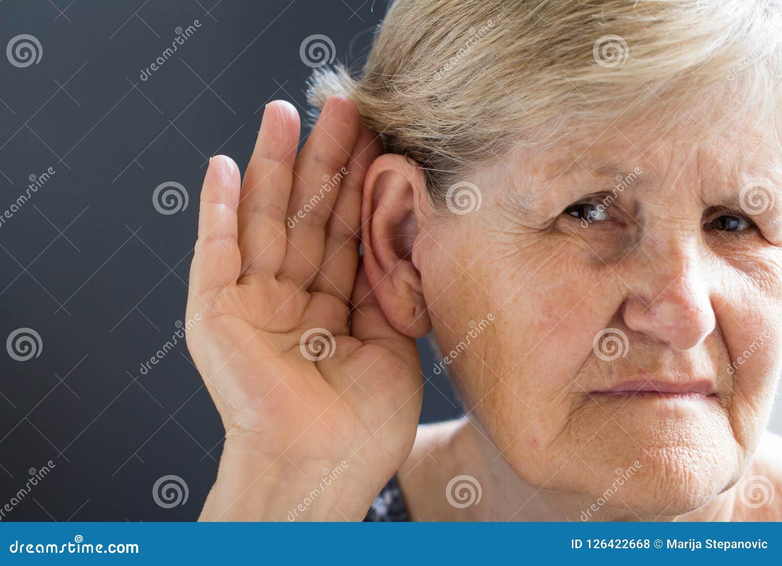 Mulher idosa com perda da audição no fundo cinzento Relativo à idade