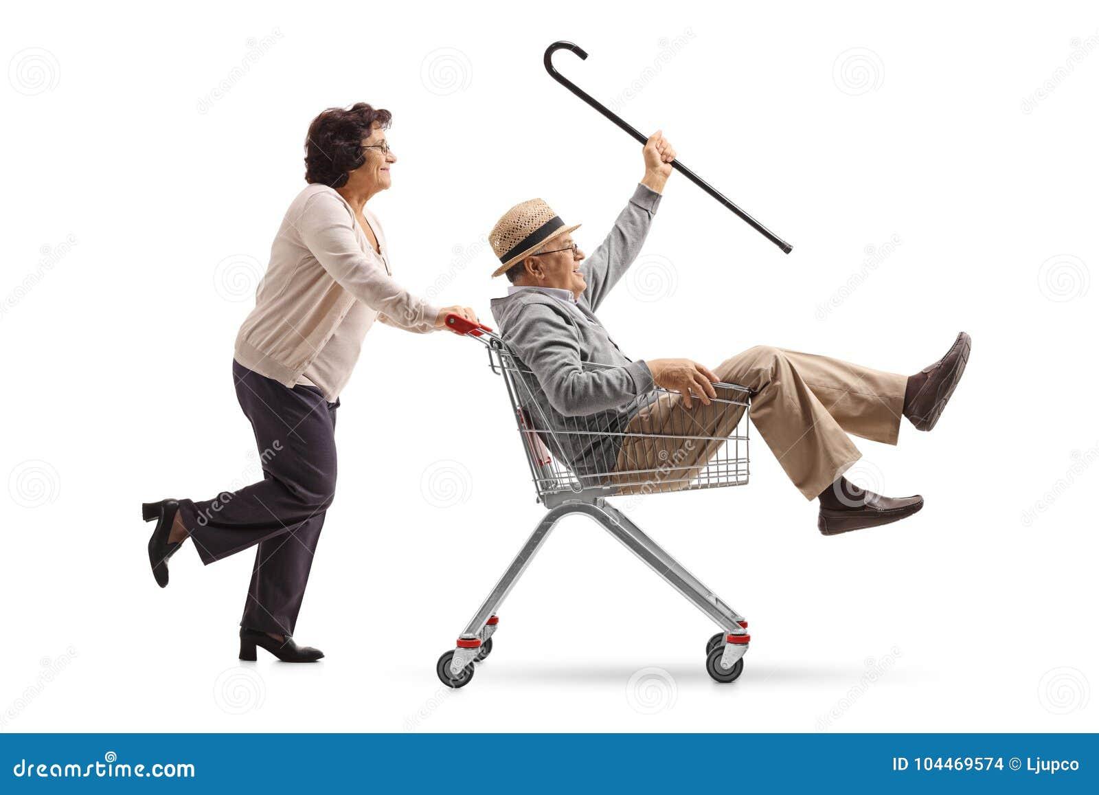 Mulher idosa que empurra um carrinho de compras com um insid superior da equitação