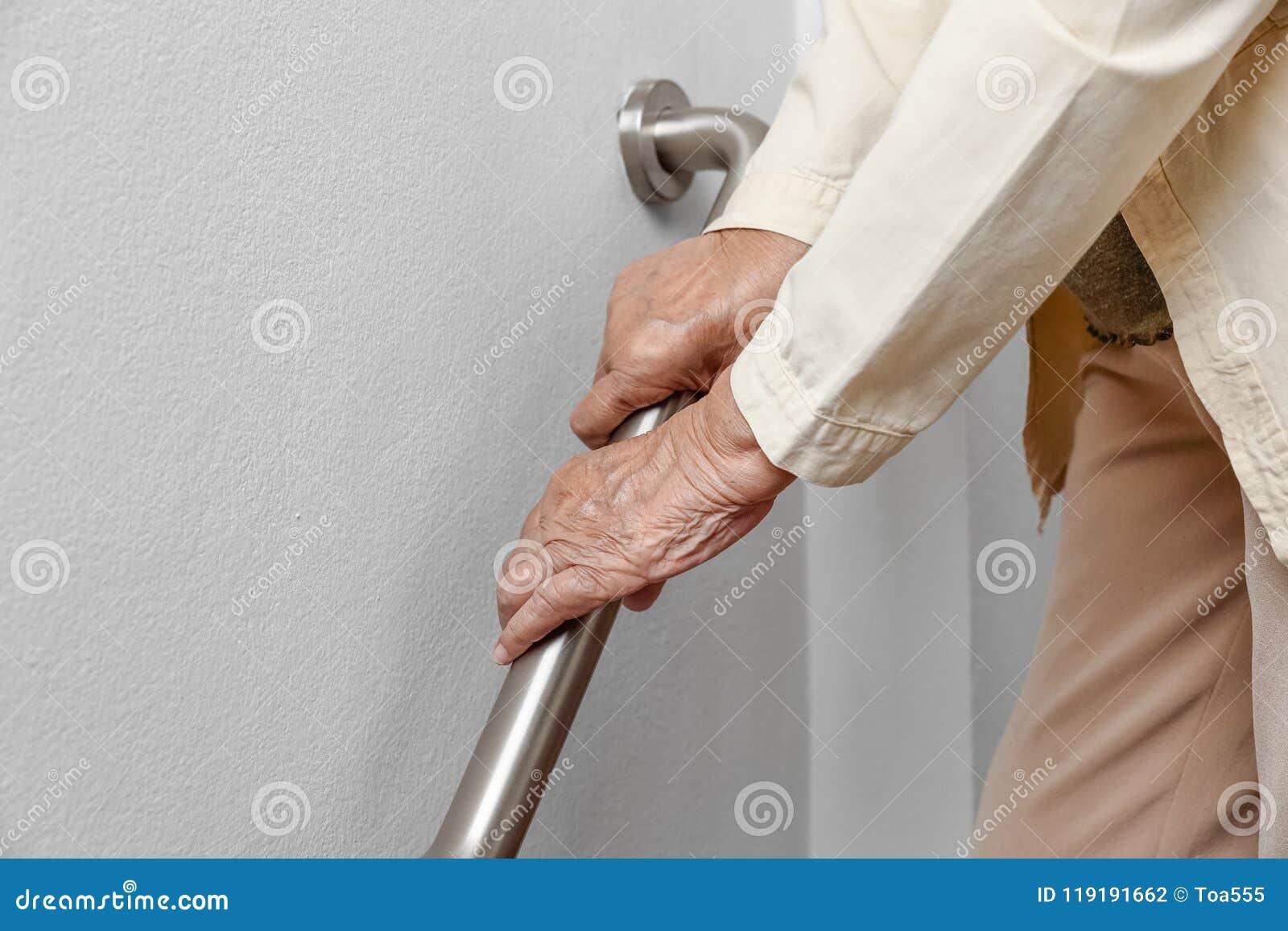 A mulher idosa que guarda sobre o corrimão para a caminhada da segurança pisa