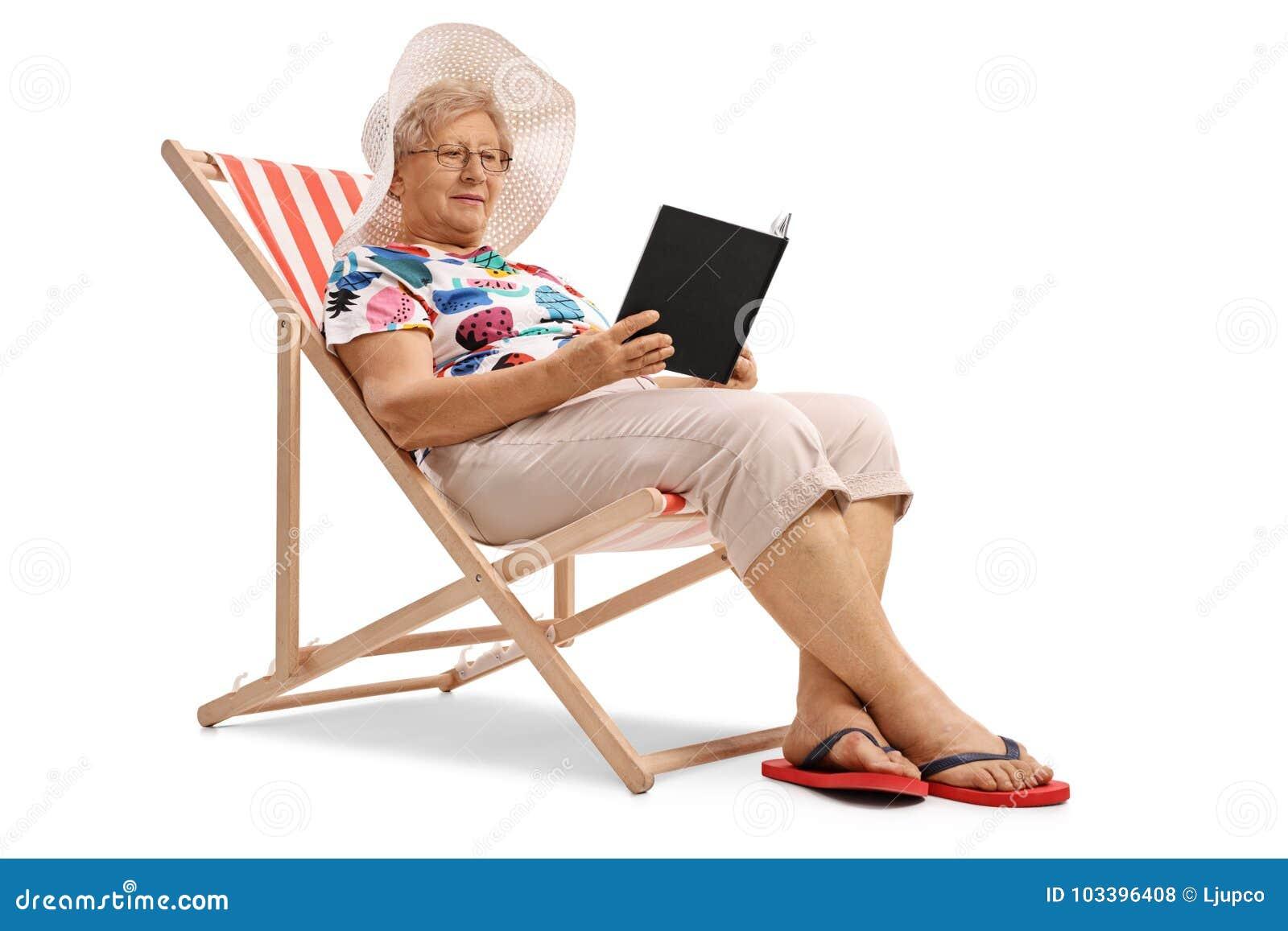 Mulher idosa que senta-se em uma cadeira de plataforma e que lê um livro