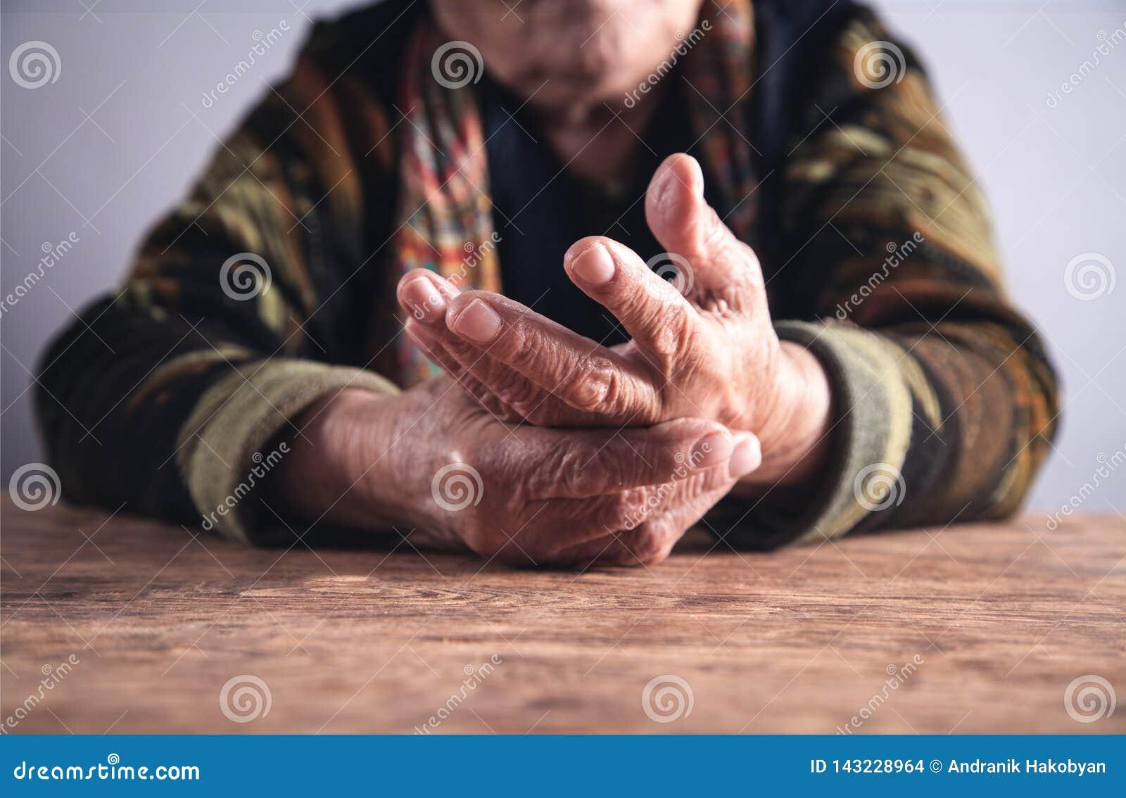 Mulher idosa que sofre da dor à disposição arthritis