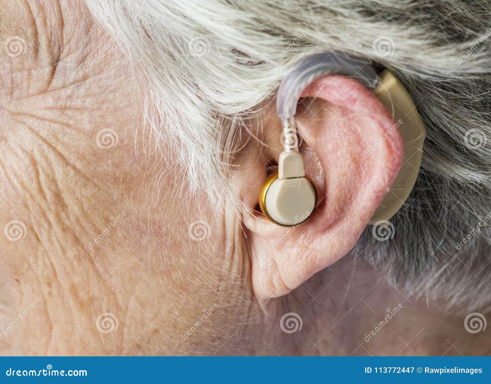 Mulher idosa que veste uma prótese auditiva