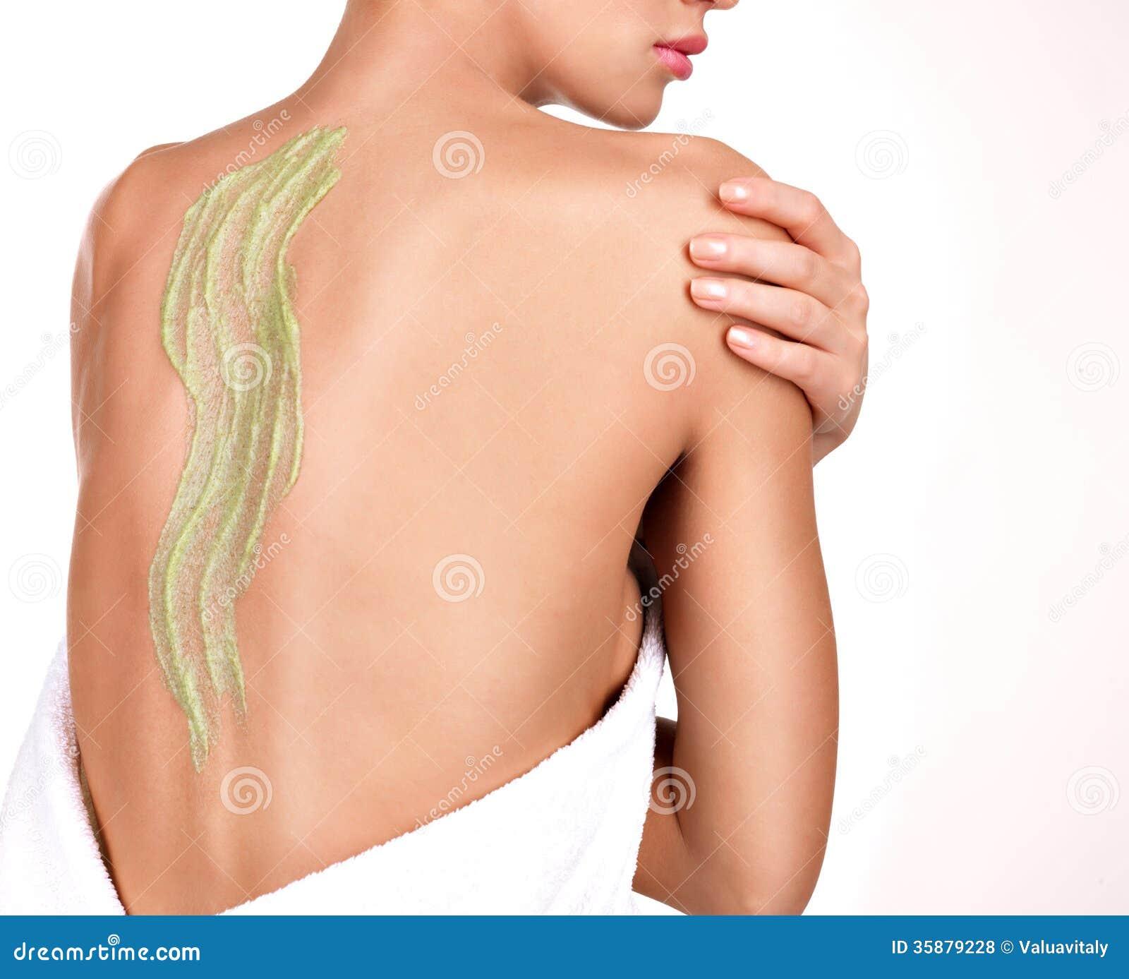A mulher importa-se com a pele do corpo que usa o cosmético esfrega na parte traseira