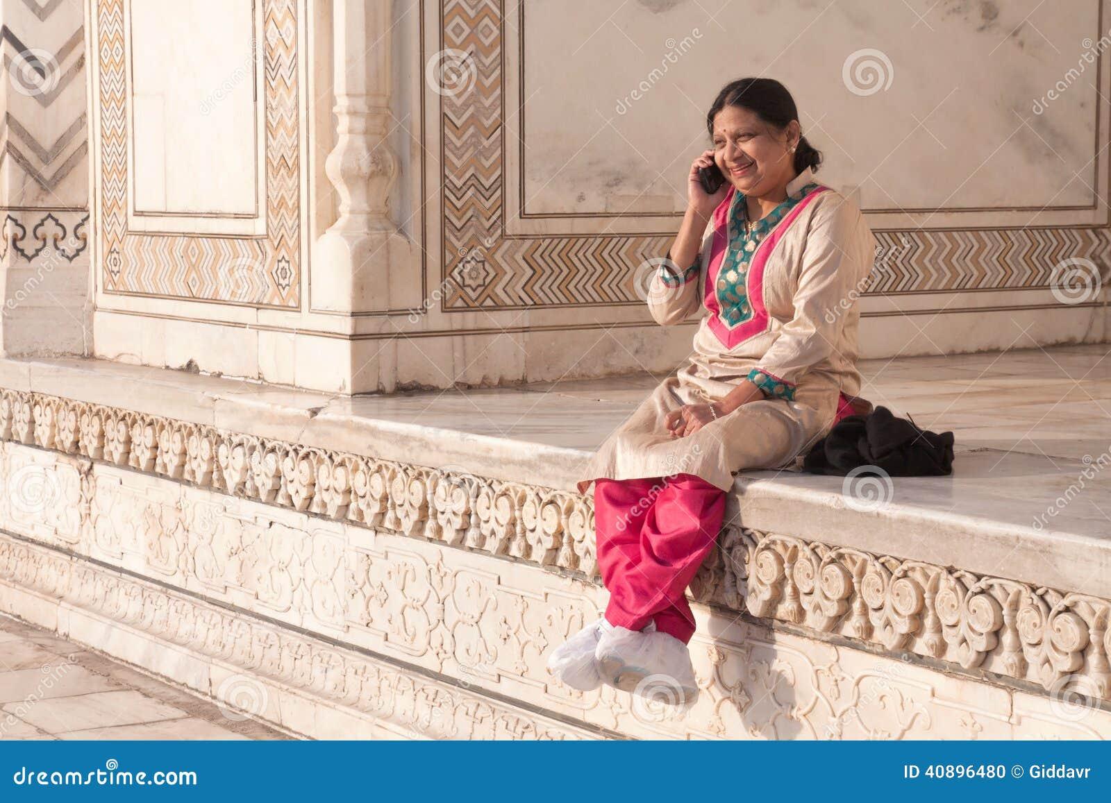 Mulher indiana tradicionalmente vestida que conversa a manhã felizmente brilhante taj-mahal