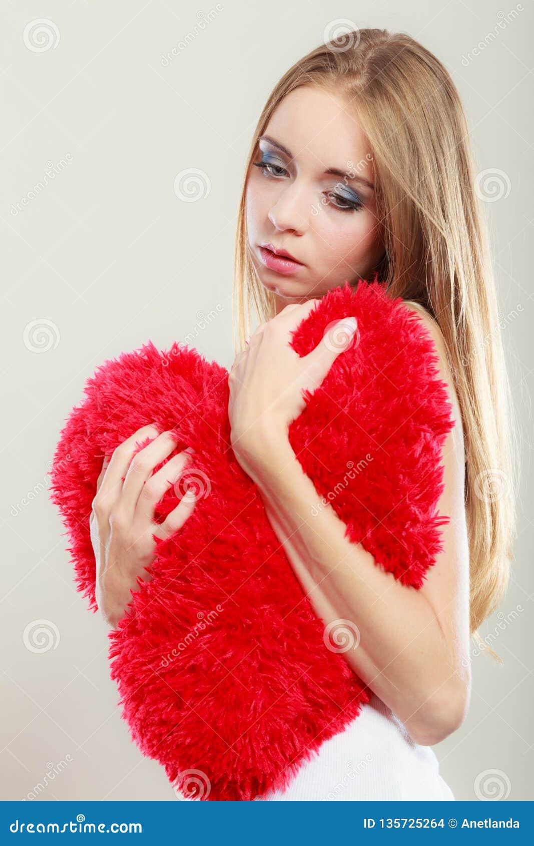 Mulher infeliz triste que guarda o descanso vermelho do coração