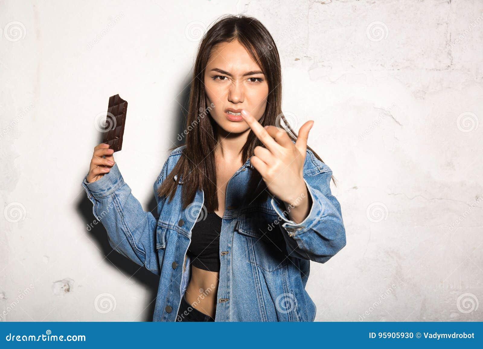 Mulher irritada do moderno que come o chocolate que mostra o dedo médio