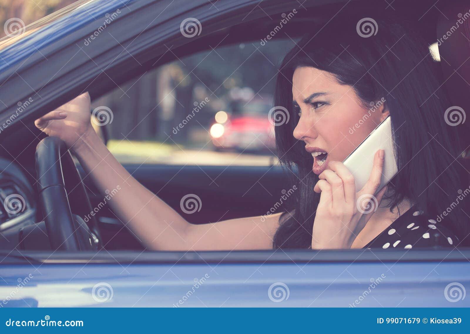Mulher irritada do motorista do perfil lateral que fala no telefone celular