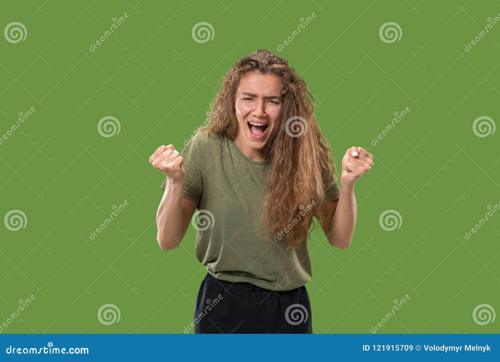 A mulher irritada emocional nova que grita no fundo verde do estúdio
