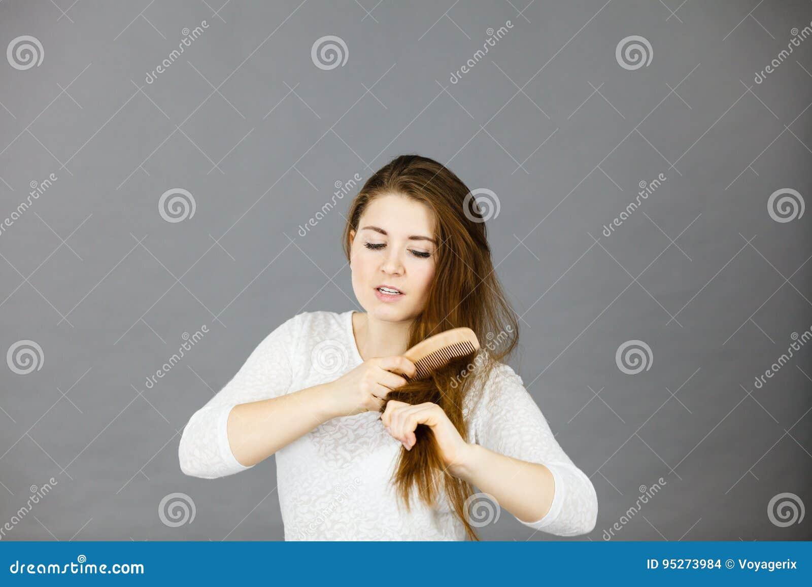 Mulher irritada que tenta escovar seu cabelo