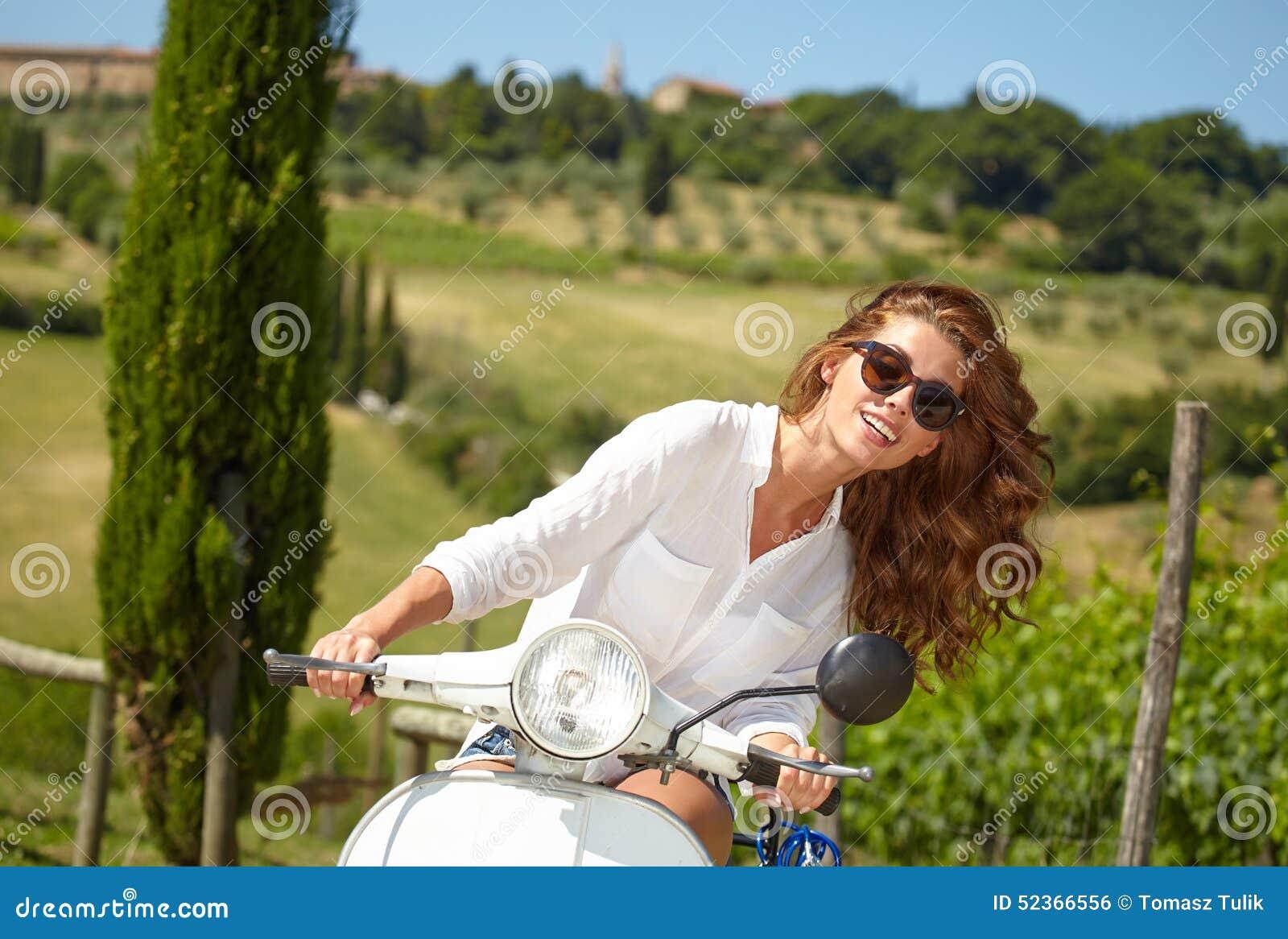 Mulher italiana que senta-se em um  trotinette  italiano