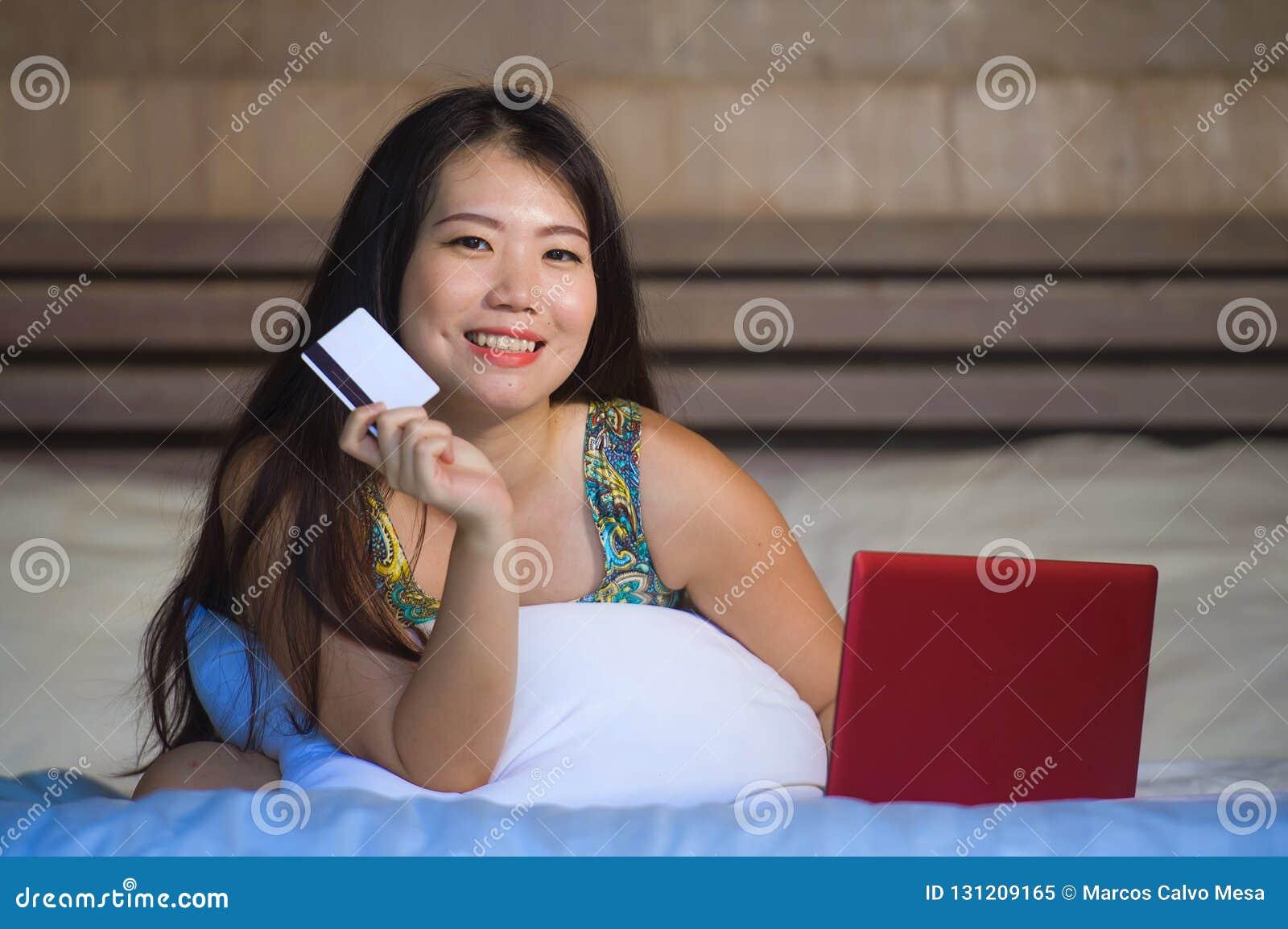 Mulher japonesa asiática feliz bonita nova que usa Internet banking do cartão de crédito no laptop em casa no e em linha da compr