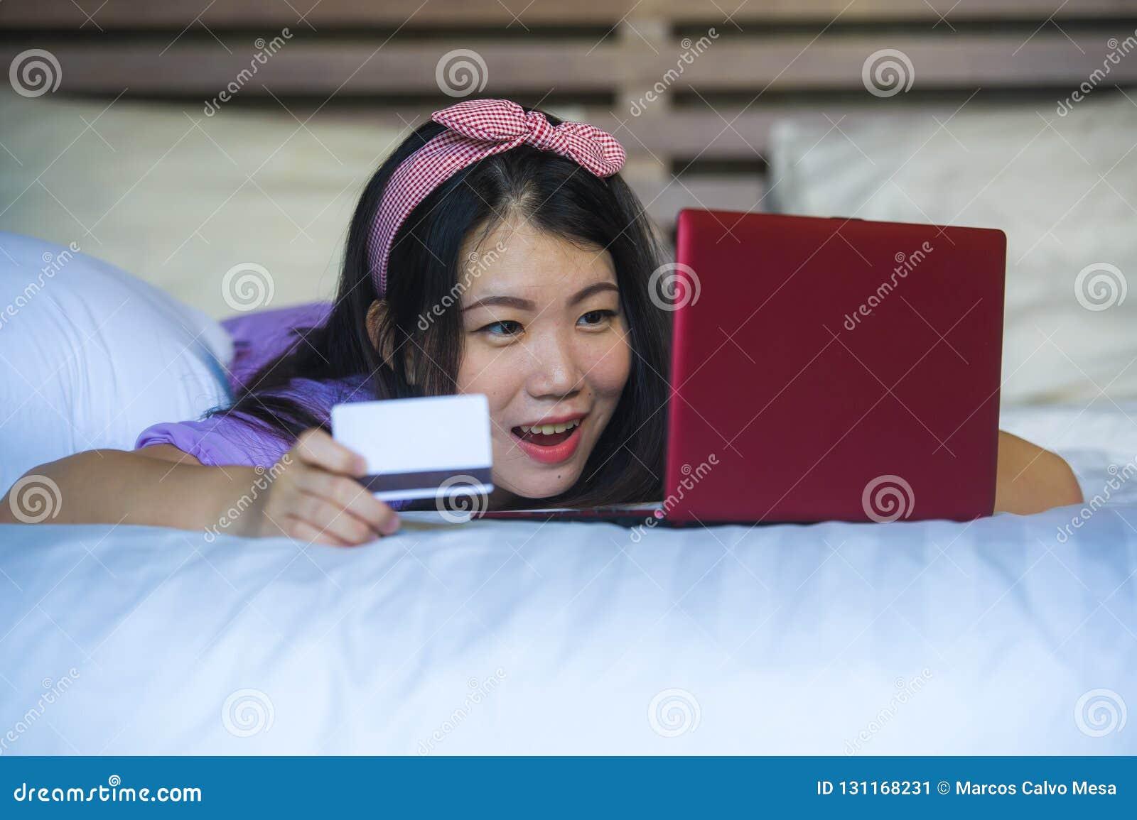 Mulher japonesa asiática feliz bonita nova que usa Internet banking do cartão de crédito no laptop em casa na cama o de compra de