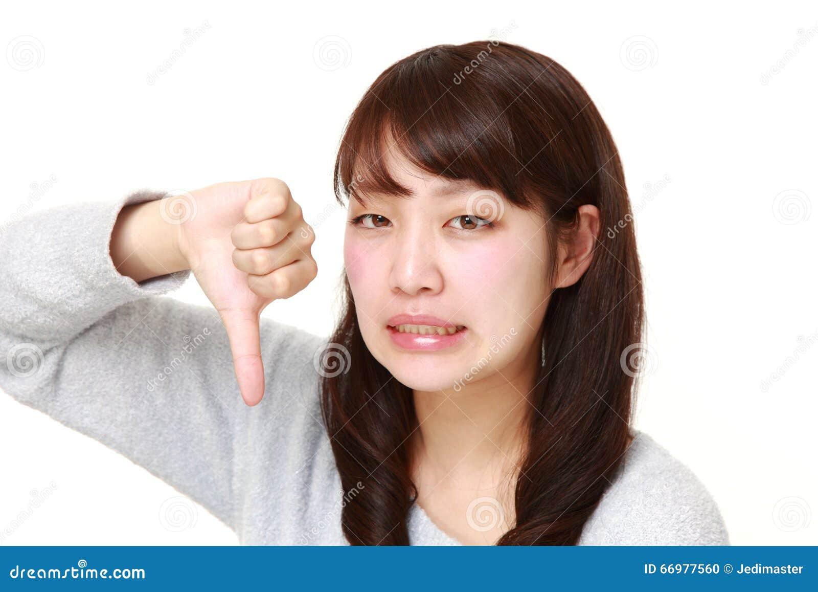 A mulher japonesa nova com polegares gesticula para baixo