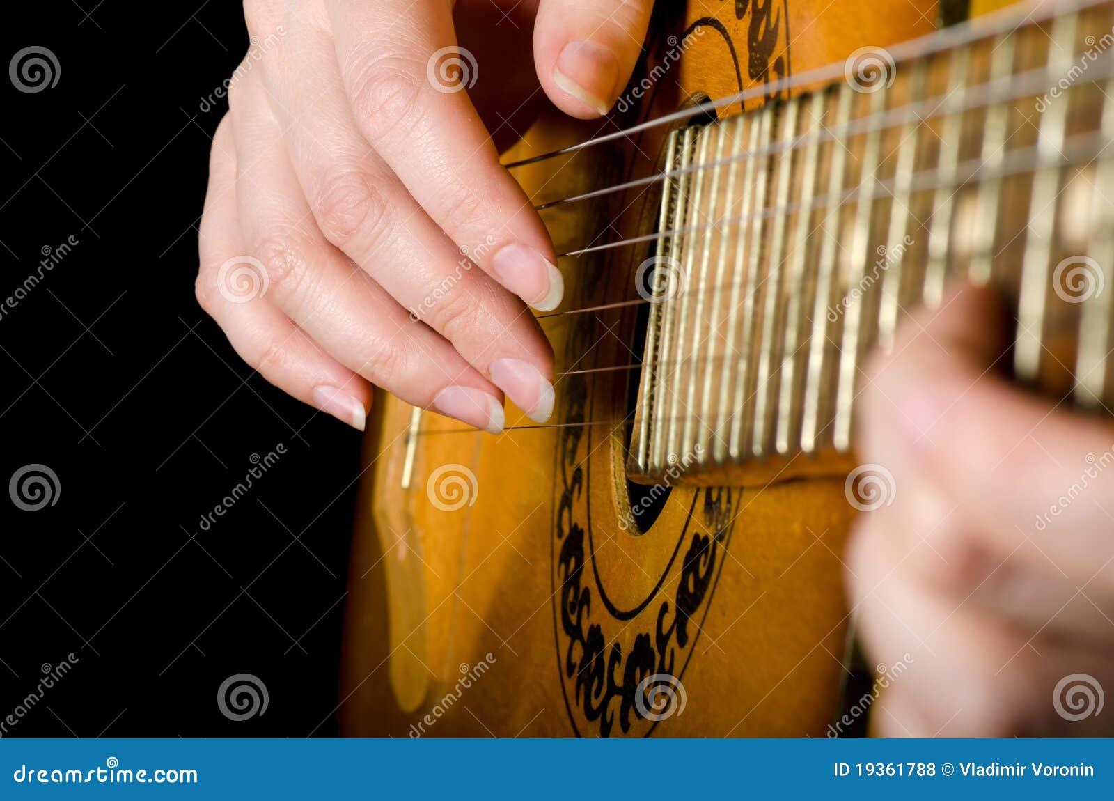 A mulher joga uma guitarra acústica