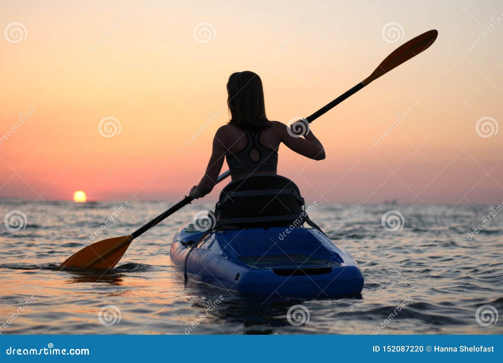 Mulher Kayaking no caiaque, enfileiramento da menina na água de um mar calmo