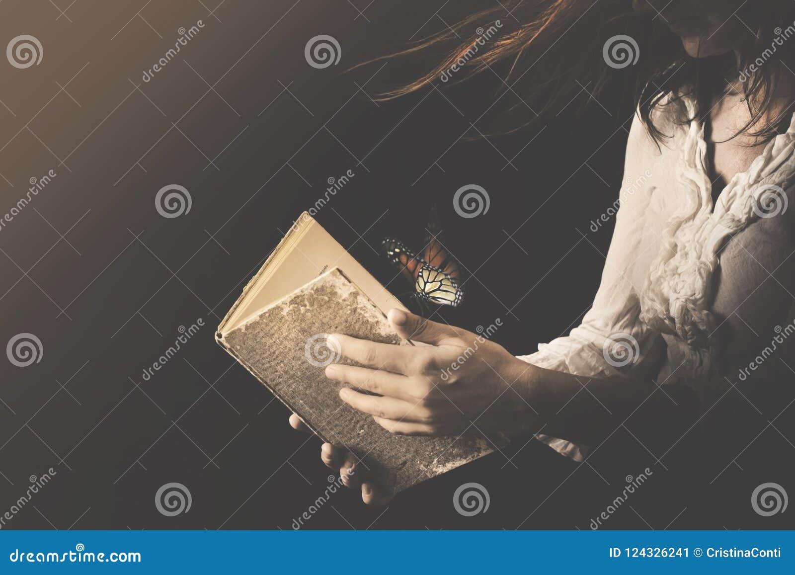 A mulher lê um livro aonde as borboletas saiam