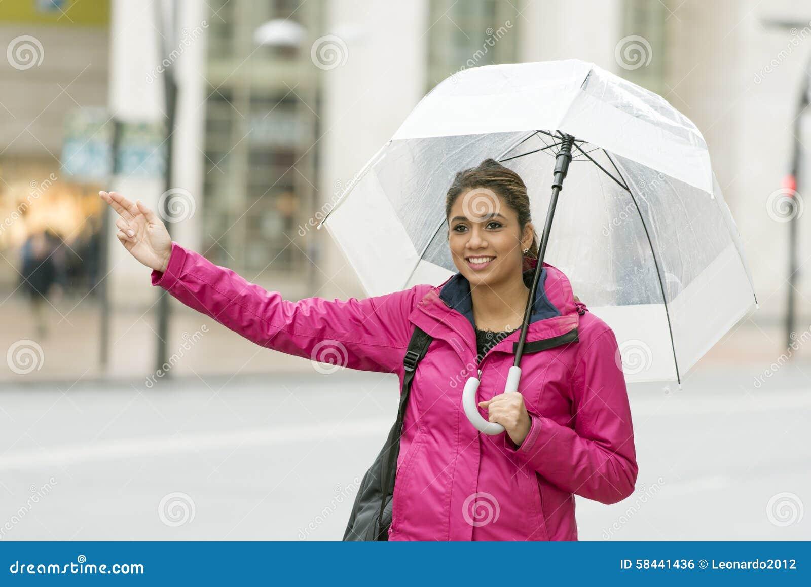 Mulher latin bonita com guarda-chuva que viaja na rua