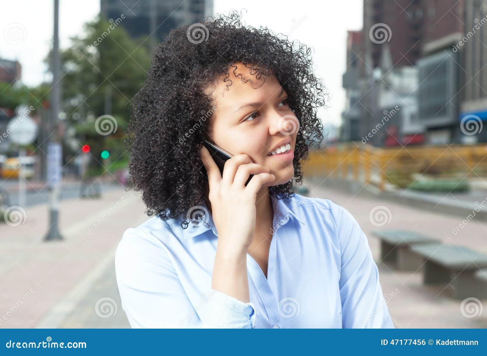 Mulher latino-americano atrativa na cidade no telefone