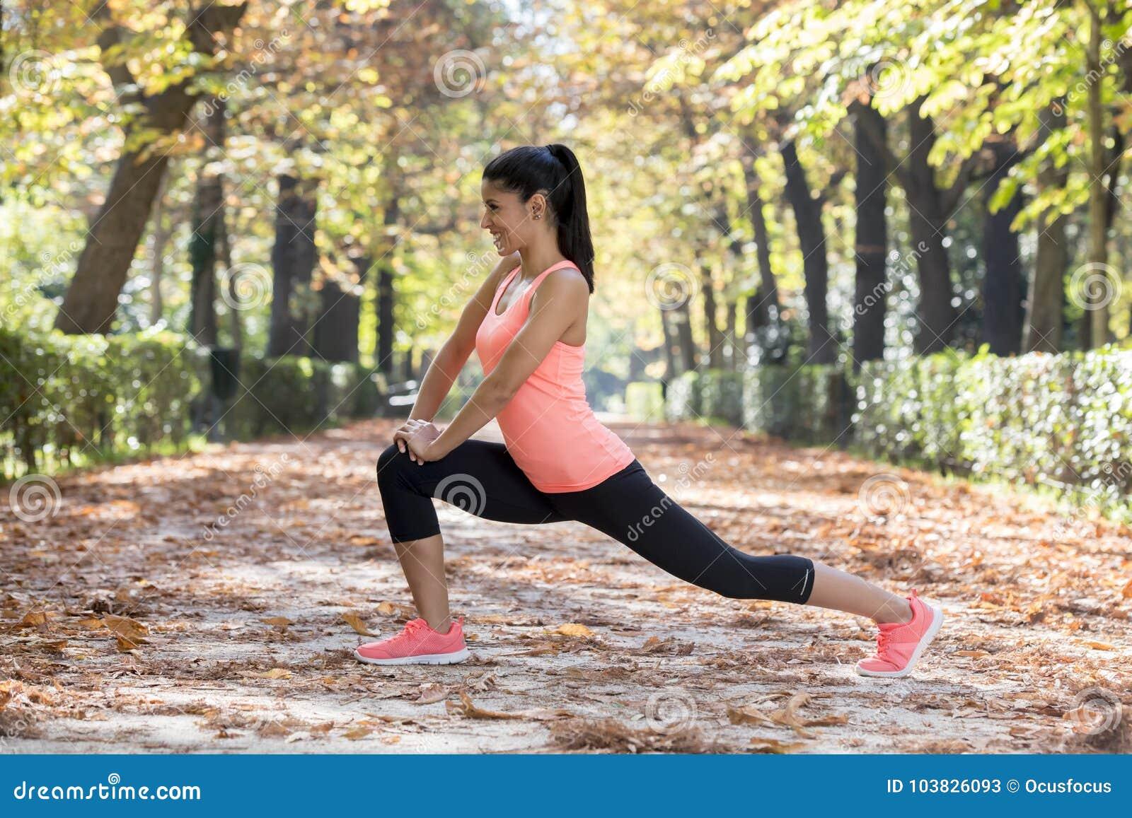 A mulher latino-americano bonita do esporte no sportswear que estica a flexibilidade fazendo feliz em seguida de sorriso do corpo