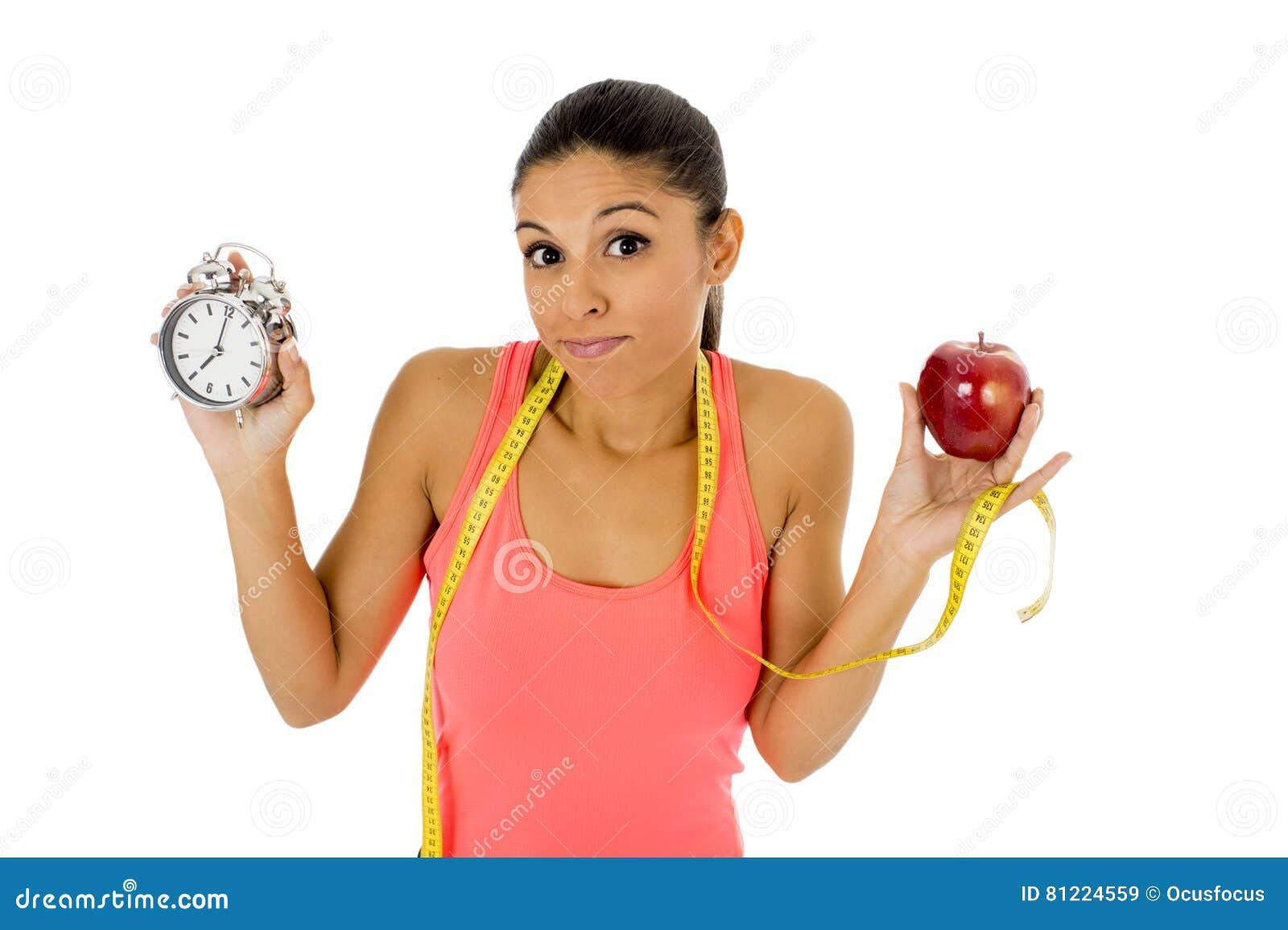 Mulher latino-americano bonita e apta que guarda a medida da fita do fruto e do taylor da maçã do despertador