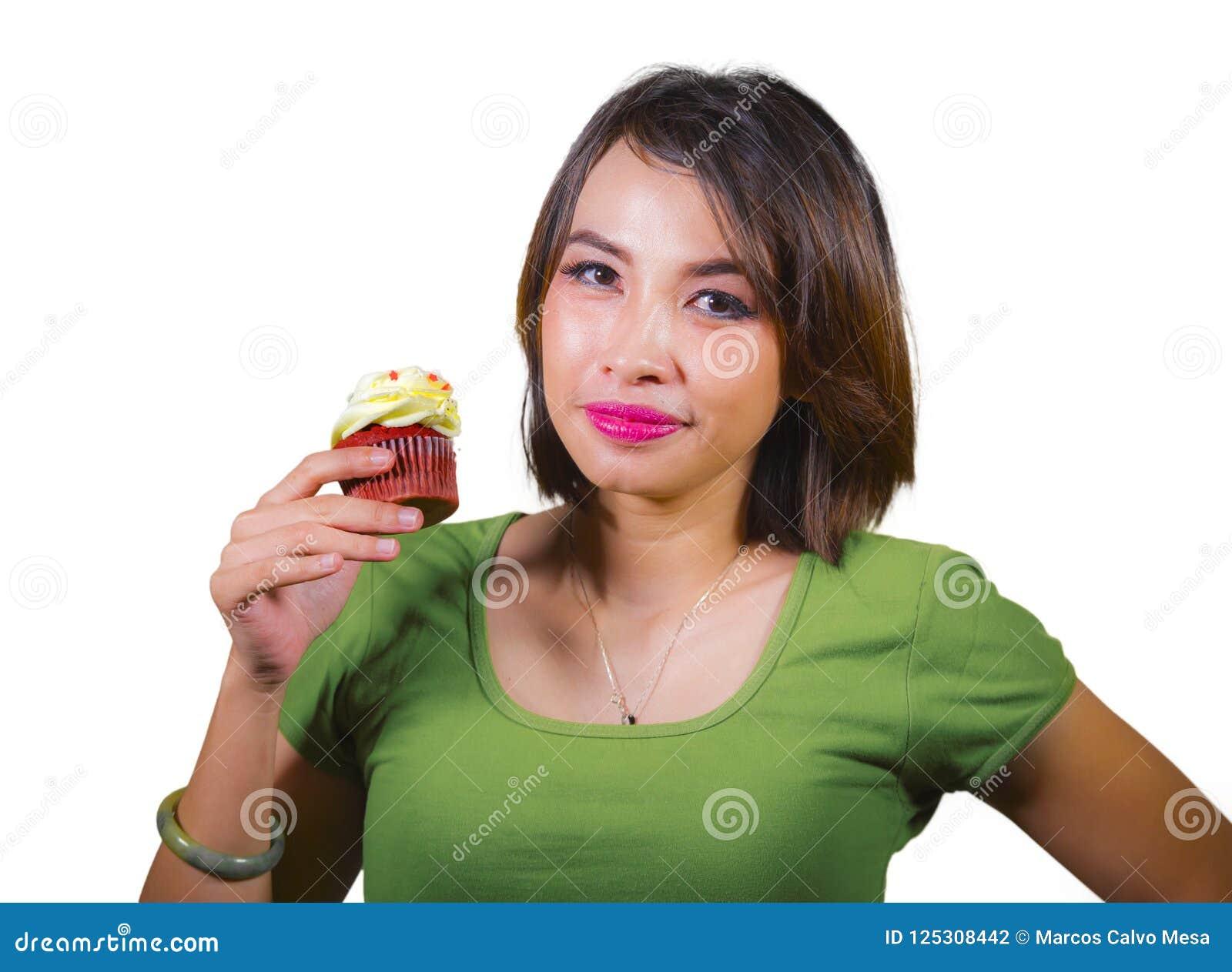 Mulher latino-americano bonita e feliz nova que come o queque açucarado amarelo saboroso e delicioso que levanta no fundo isolado