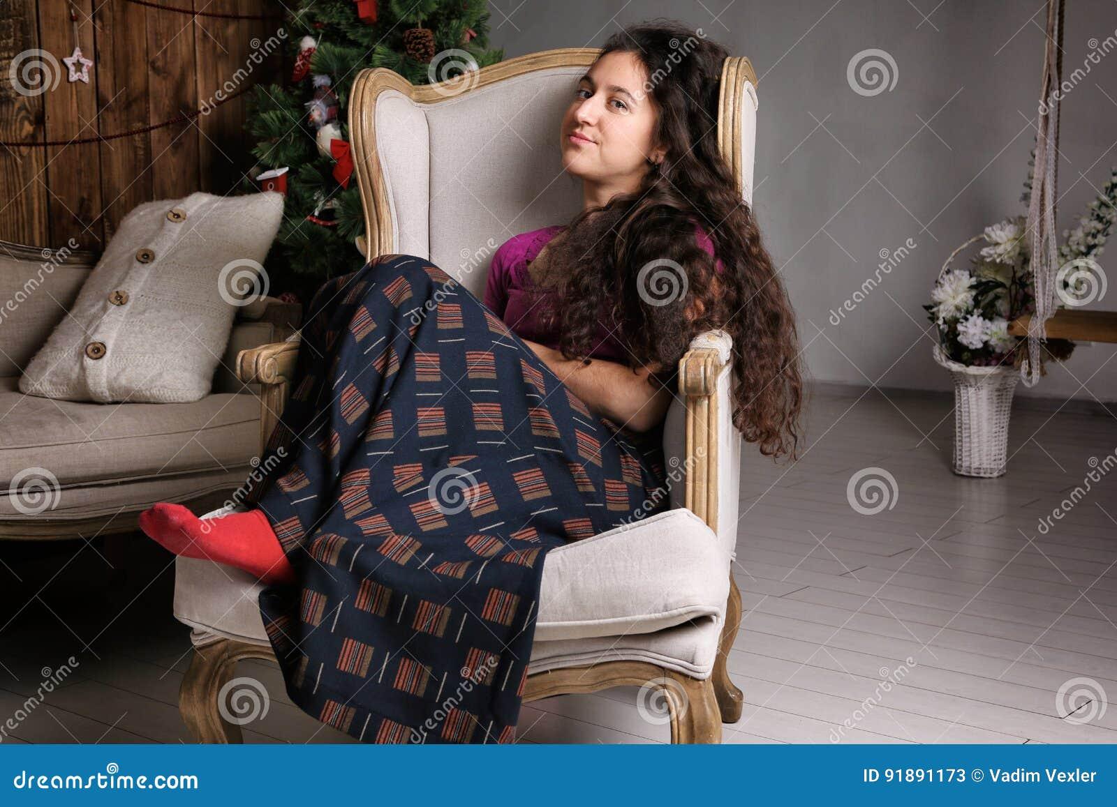 Mulher latino-americano nova que senta-se na cadeira na celebração interior e esperando rústica