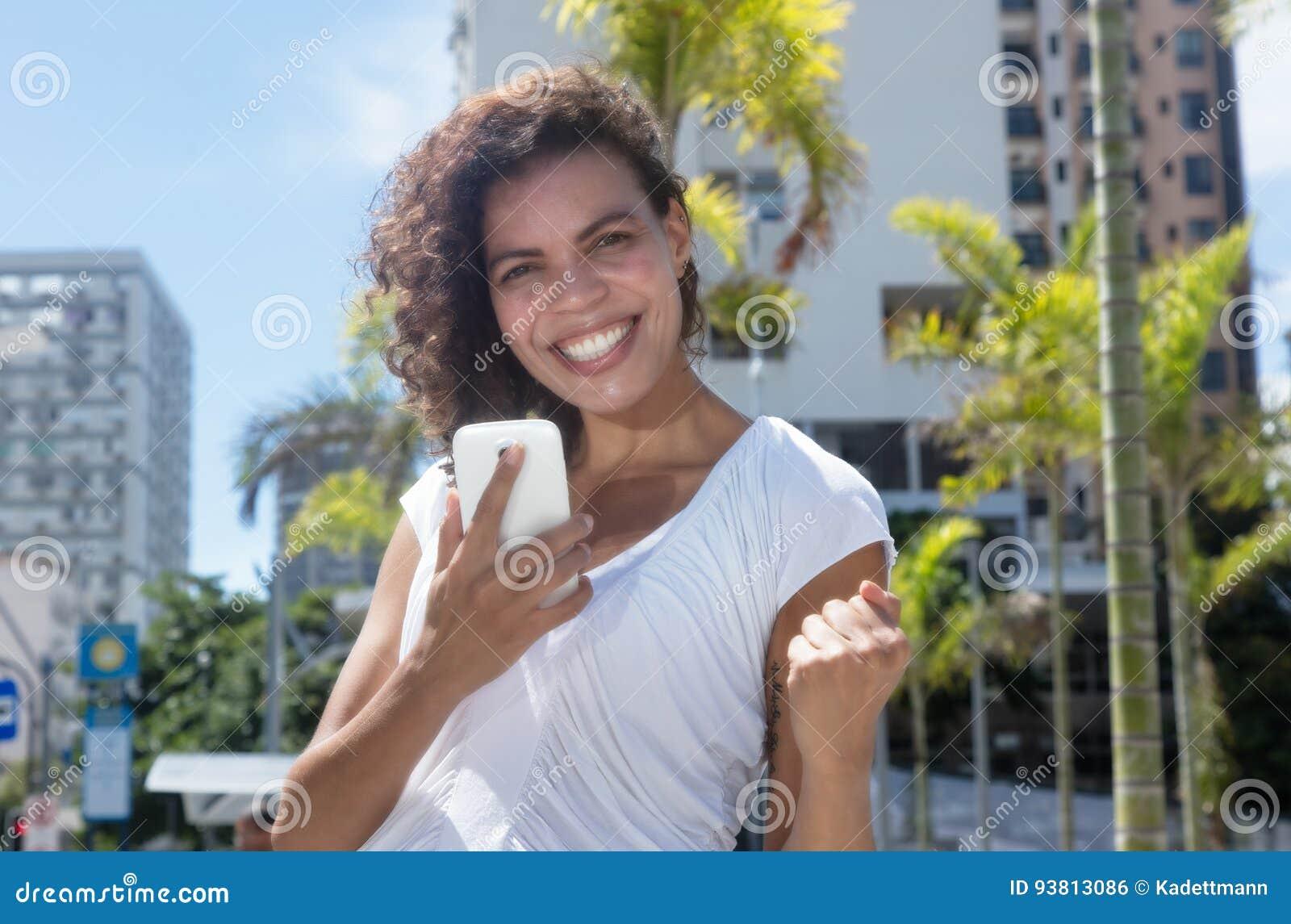 Mulher latino-americano que recebe a boa notícia pelo telefone