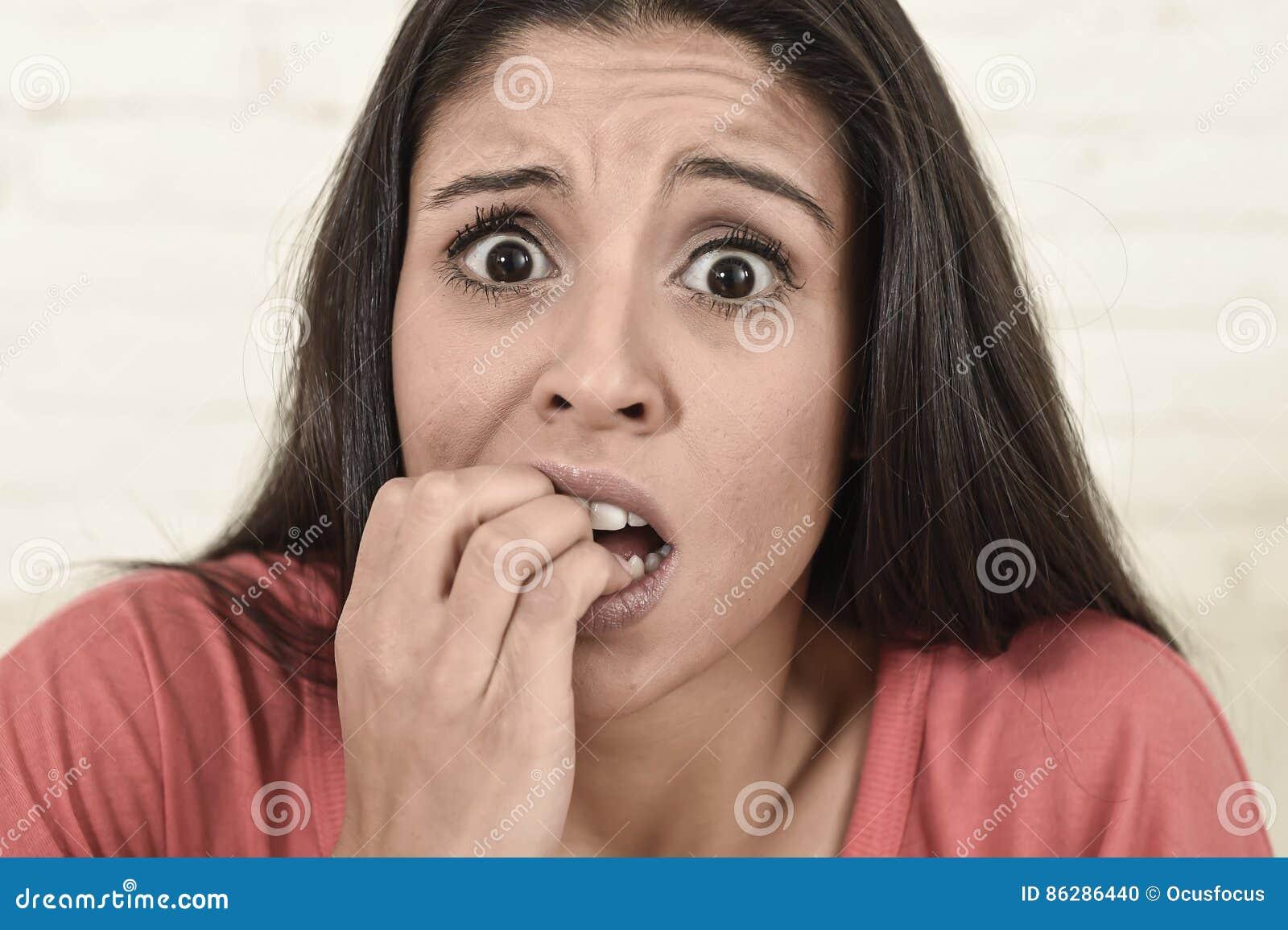 Mulher latino que senta em casa o sofá do sofá no filme de terror assustador de observação da televisão da sala de visitas