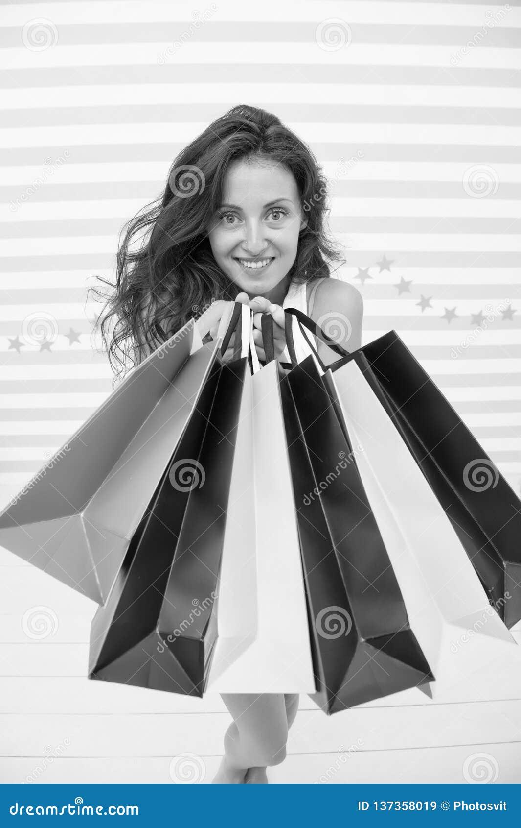 A mulher leva o fundo listrado sacos de compras do grupo Tipo favorito finalmente comprado Vendas da loja das pontas Menina satis