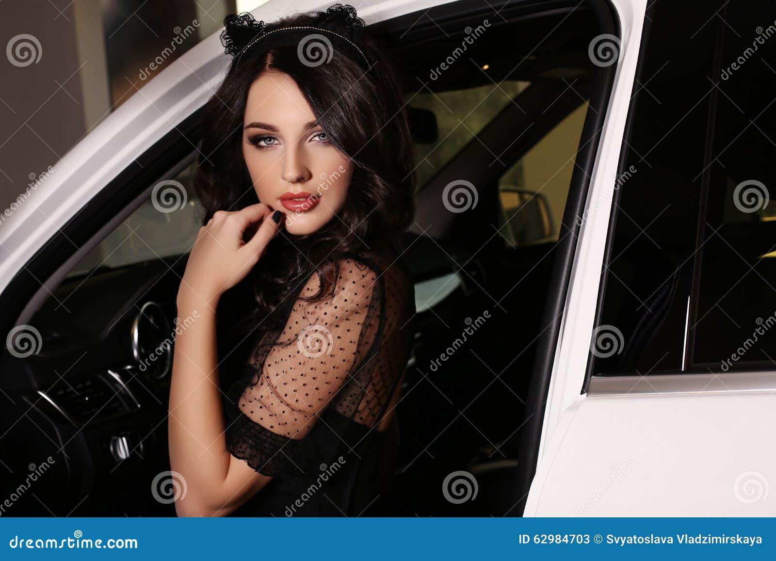 A mulher lindo com cabelo escuro veste o vestido luxuoso, levantando no carro branco