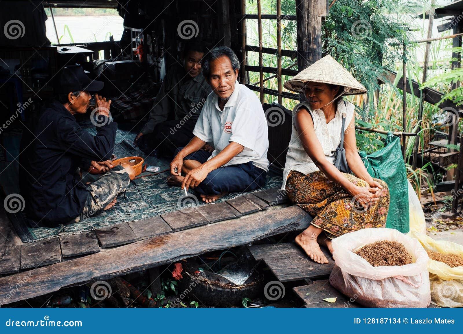 A mulher local em um chapéu cônico tradicional que vende o cigarro no mercado da vila ao lado do Mekong River com seu assento da
