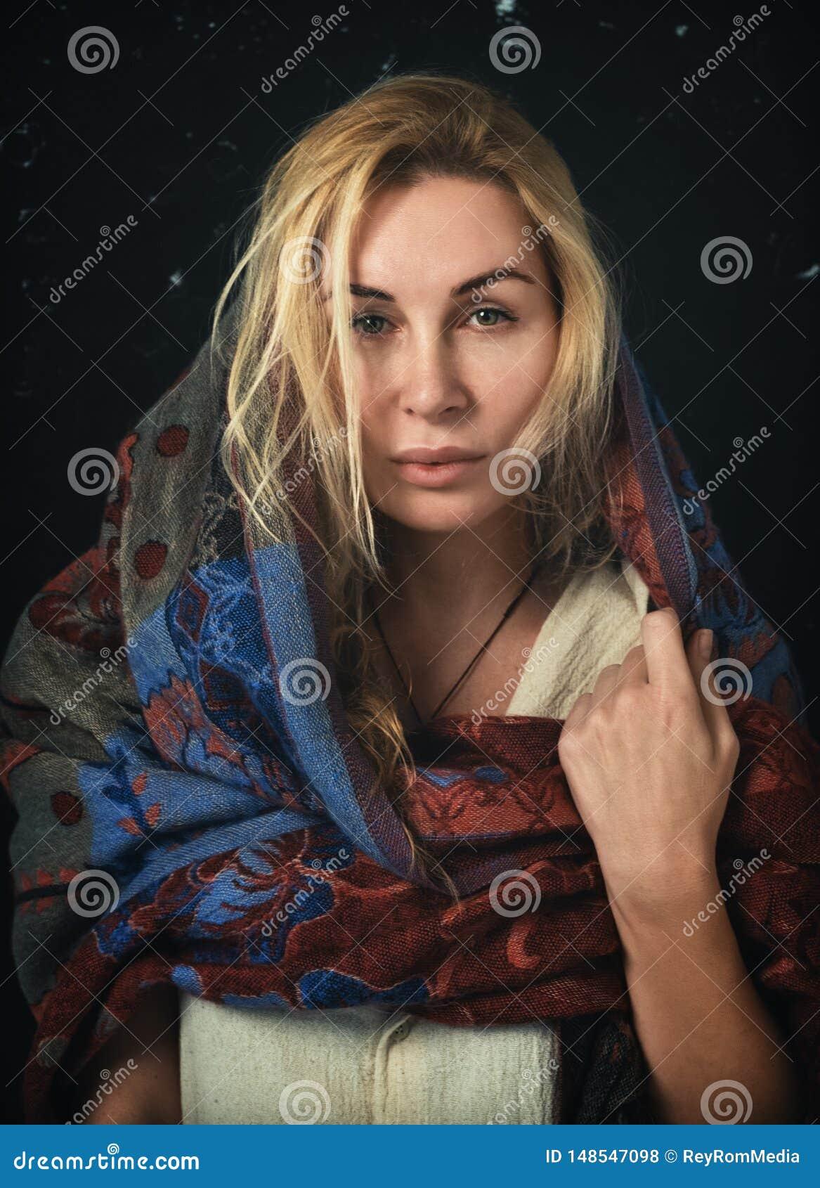 Mulher loura à moda com um lenço que cobre seus cabeça e ombros