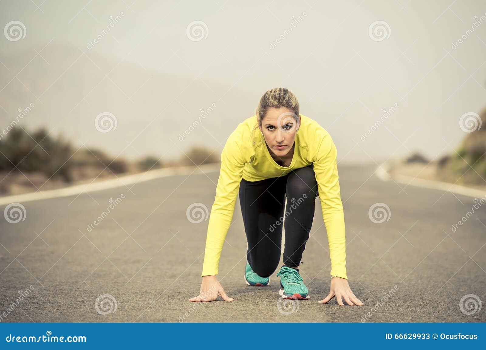 Mulher loura atrativa do esporte pronta para começar correr a raça do treinamento da prática que começa na paisagem da montanha d