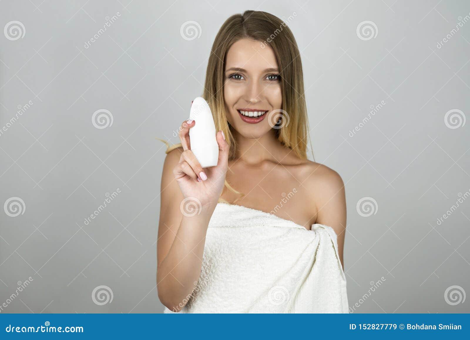 Mulher loura bonita de sorriso no antiperspirante branco da terra arrendada de toalha em seu fundo branco isolado mão
