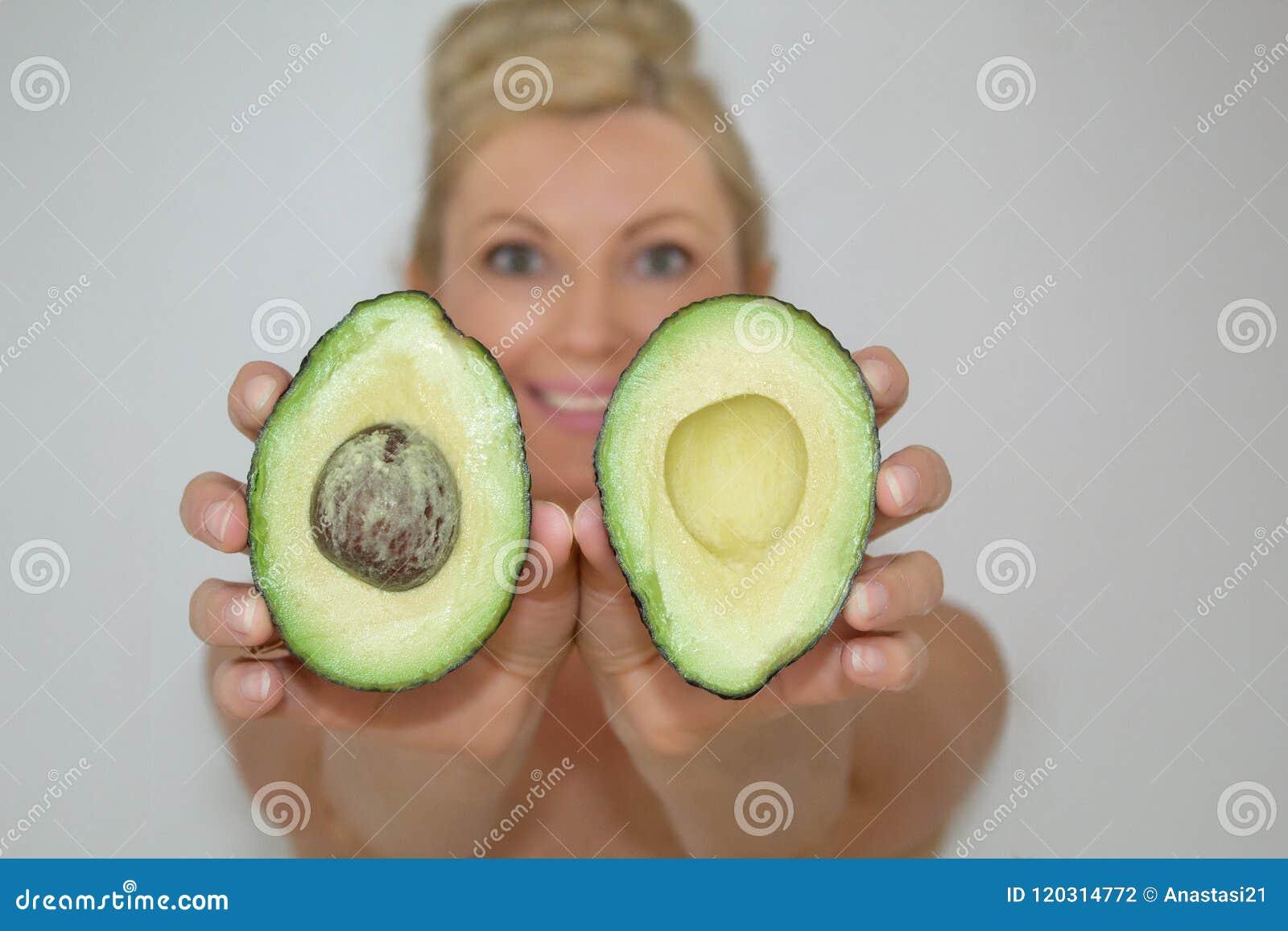 Mulher loura bonita do abacate na frente da câmera, close-up
