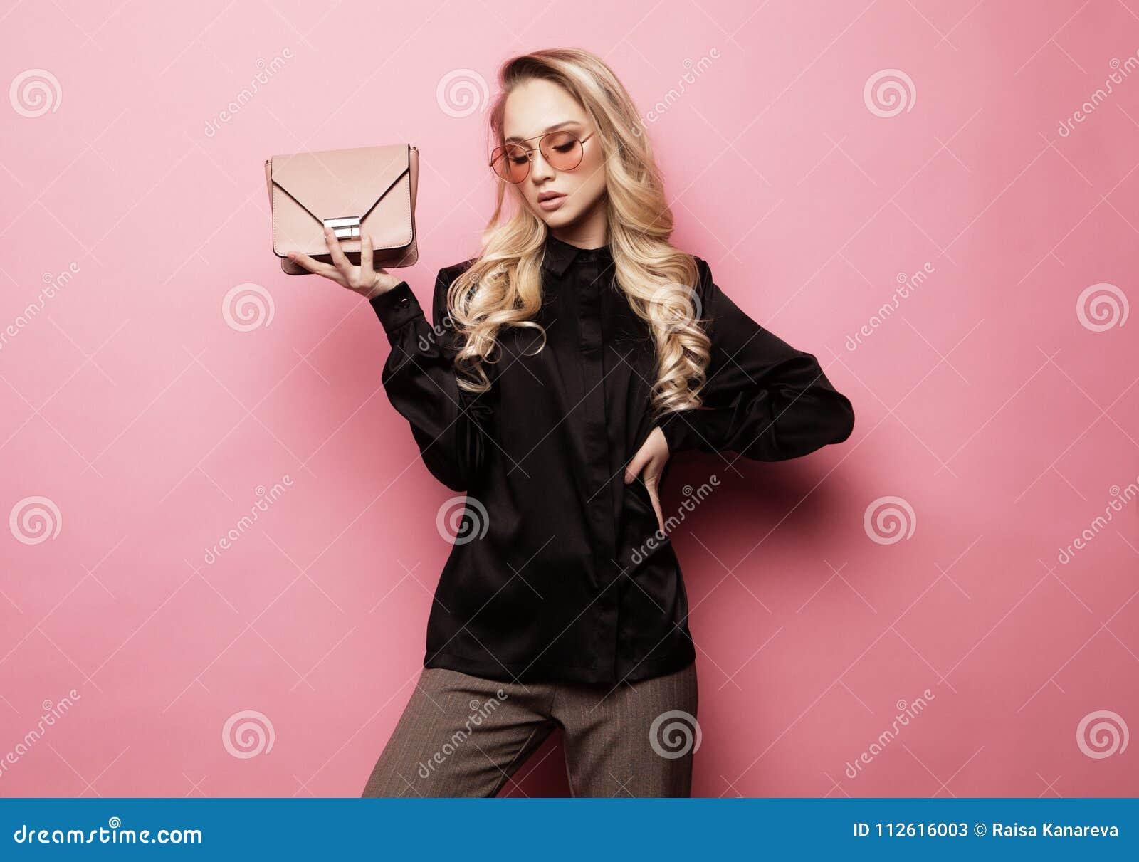 Mulher loura bonita em uma blusa e nas calças que vestem os vidros, guardando a bolsa que levanta sobre o fundo cor-de-rosa