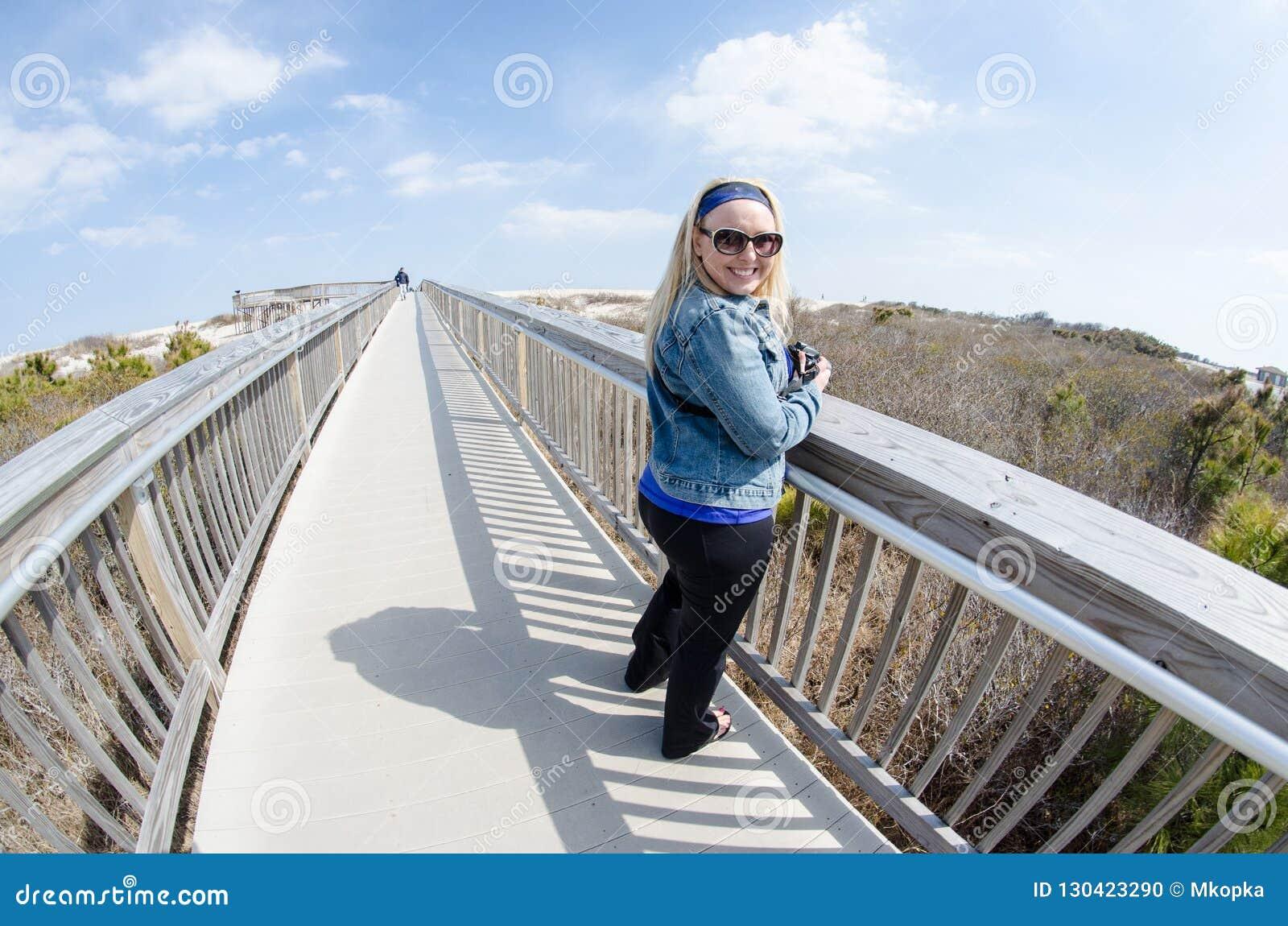 A mulher loura bonita está no passeio à beira mar elevado na ilha de Assateague