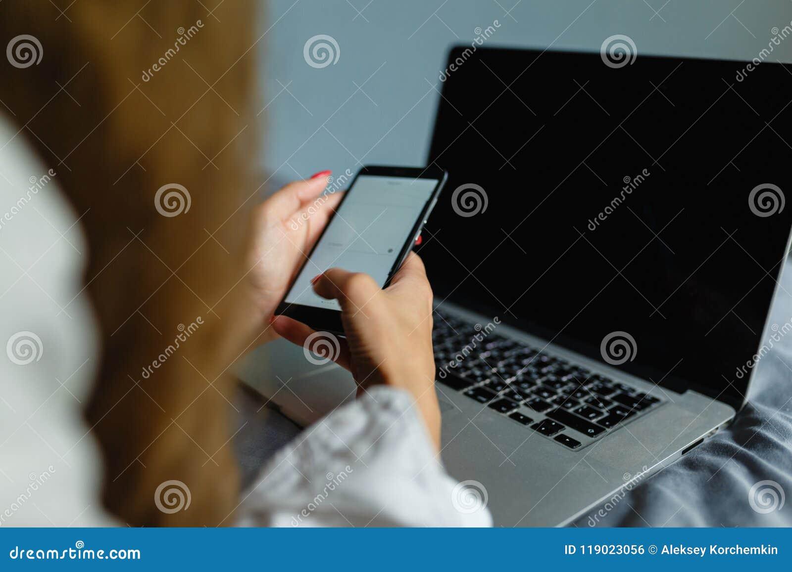 Mulher loura bonita que telefona com seu smartphone que encontra-se em sua cama ao lado de seu caderno Menina que encontra-se na