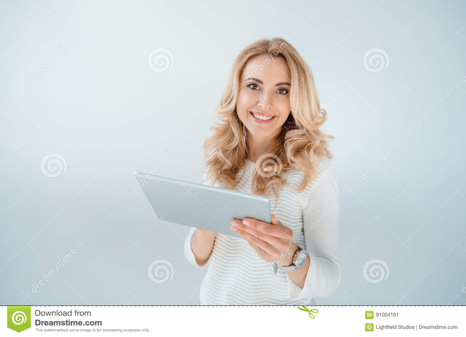 Mulher loura bonita que usa a tabuleta digital no cinza
