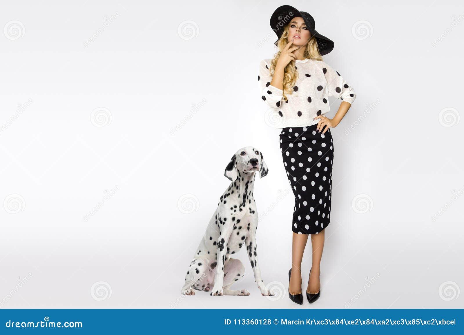 Mulher loura bonita,  sexy  em às bolinhas elegantes e um chapéu, estando em um fundo branco ao lado de um cão dalmatian