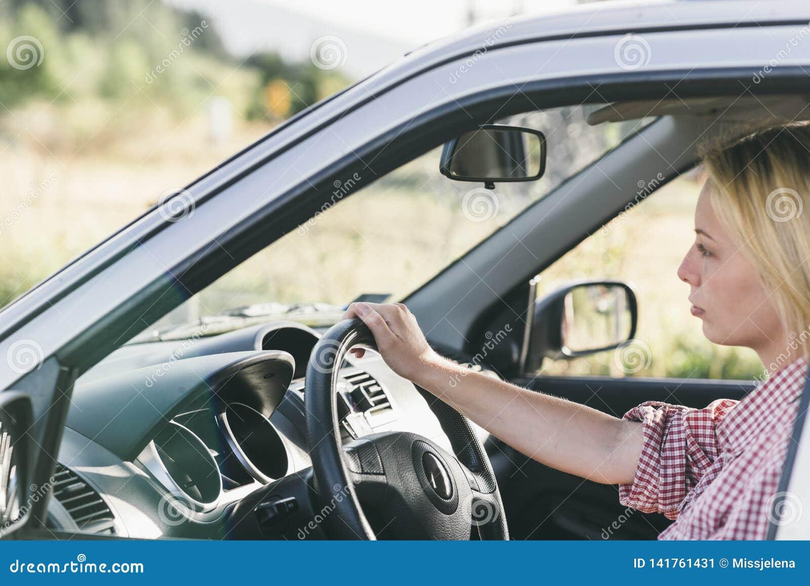 Mulher loura caucasiano nova que viaja pelo carro e que tem o divertimento em sua viagem das férias de verão Menina feliz que con